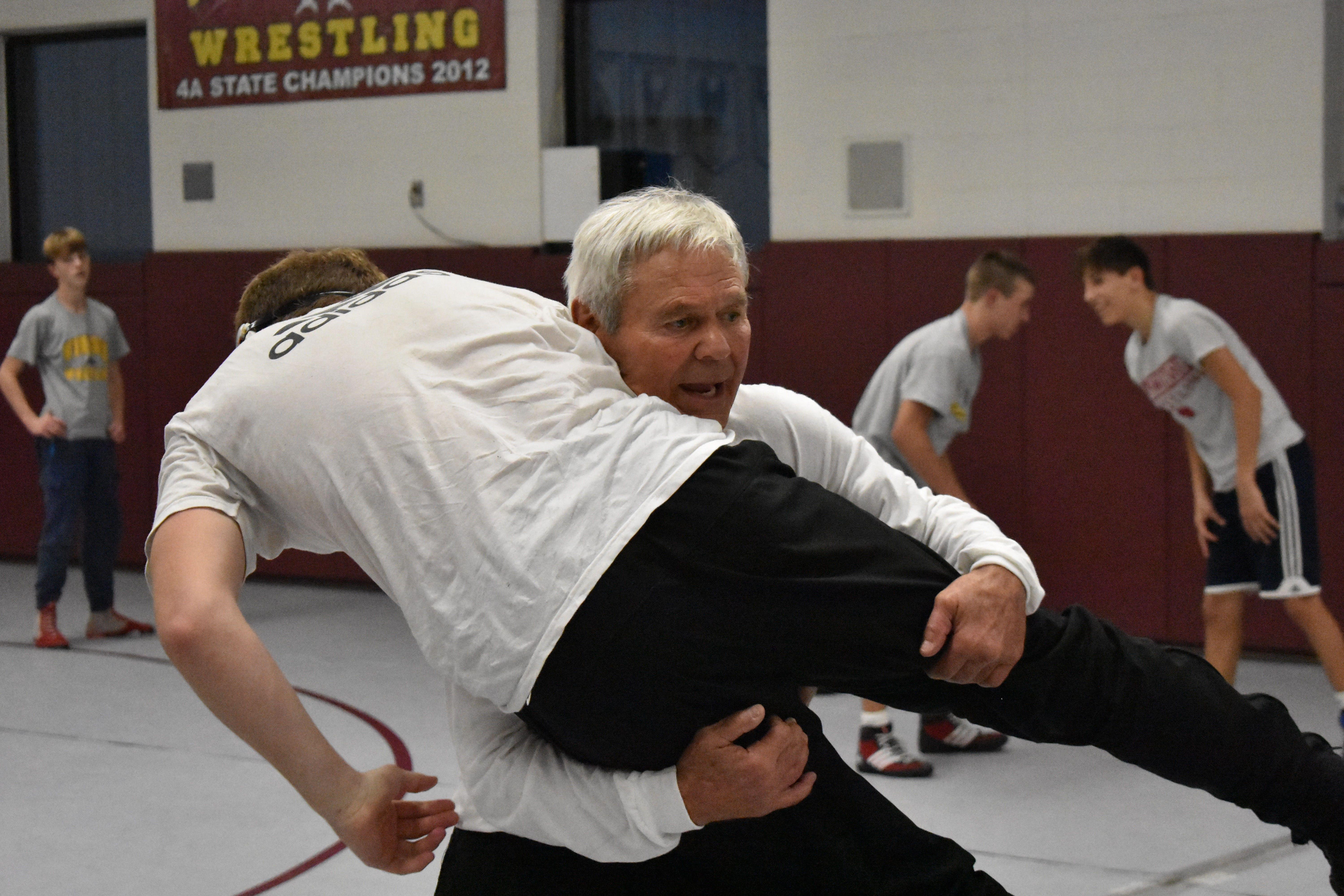 Wrestling trainer instructs 2 students