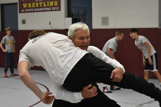 Windsor assistant wrestling coach Milo Trusty, 73, demonstrates a move during a practice Wednesday in the school's wrestling room.