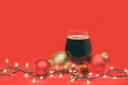 Dark Ale Beer In A Tulip Glass With Christmas Baubles And Lights On Red Background Toned