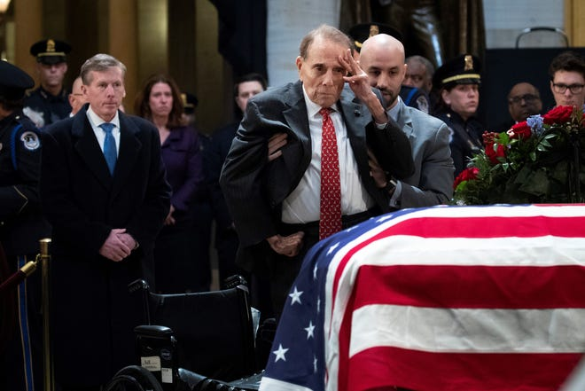 Former Sen. Bob Dole stands up and salutes the casket of the late former President George H.W. Bush as he lies in state at the U.S. Capitol, Dec. 4, in Washington, D.C. A fellow WWII combat veteran, Bush served as a member of Congress from Texas, ambassador to the United Nations, director of the CIA, vice president and 41st president of the United States.