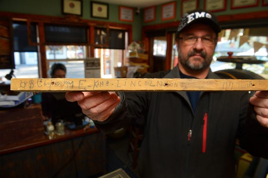 Bill Frisbee holds up a piece of wood found in the Matt King cabin which reads: H.B. Chapman; M.E. King; Lincoln, Mont.  Frisbee and Erin Dey hope to reconstruct the cabin next year on the east end of Lincoln.