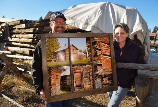 Bill Frisbee and Erin Dey stand in front of the logs belonging to the deconstructed Matt King historic log cabin, which the pair hope to reconstruct next year on the east end of Lincoln along Highway 200.