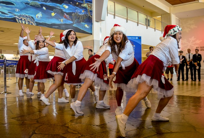 Employees perform a holiday dance to welcome guests to United Airlines' Fantasy Flight to the North Pole at the A.B. Won Pat International Airport on Friday, Dec. 7, 2018. Thirty-three Guam Special Olympians, and their guests, were presented with an experience to enjoy live entertainment, food, games, holiday cookie decorating and face paintings after a make-believe flight to visit Santa Claus and his helpers. The event was the air carrier's fifth consecutive year of sharing holiday cheer with a group of the island's deserving children. This year, the airline's Guam hub was joined by 15 other United destinations around the globe in celebrating the holiday event.