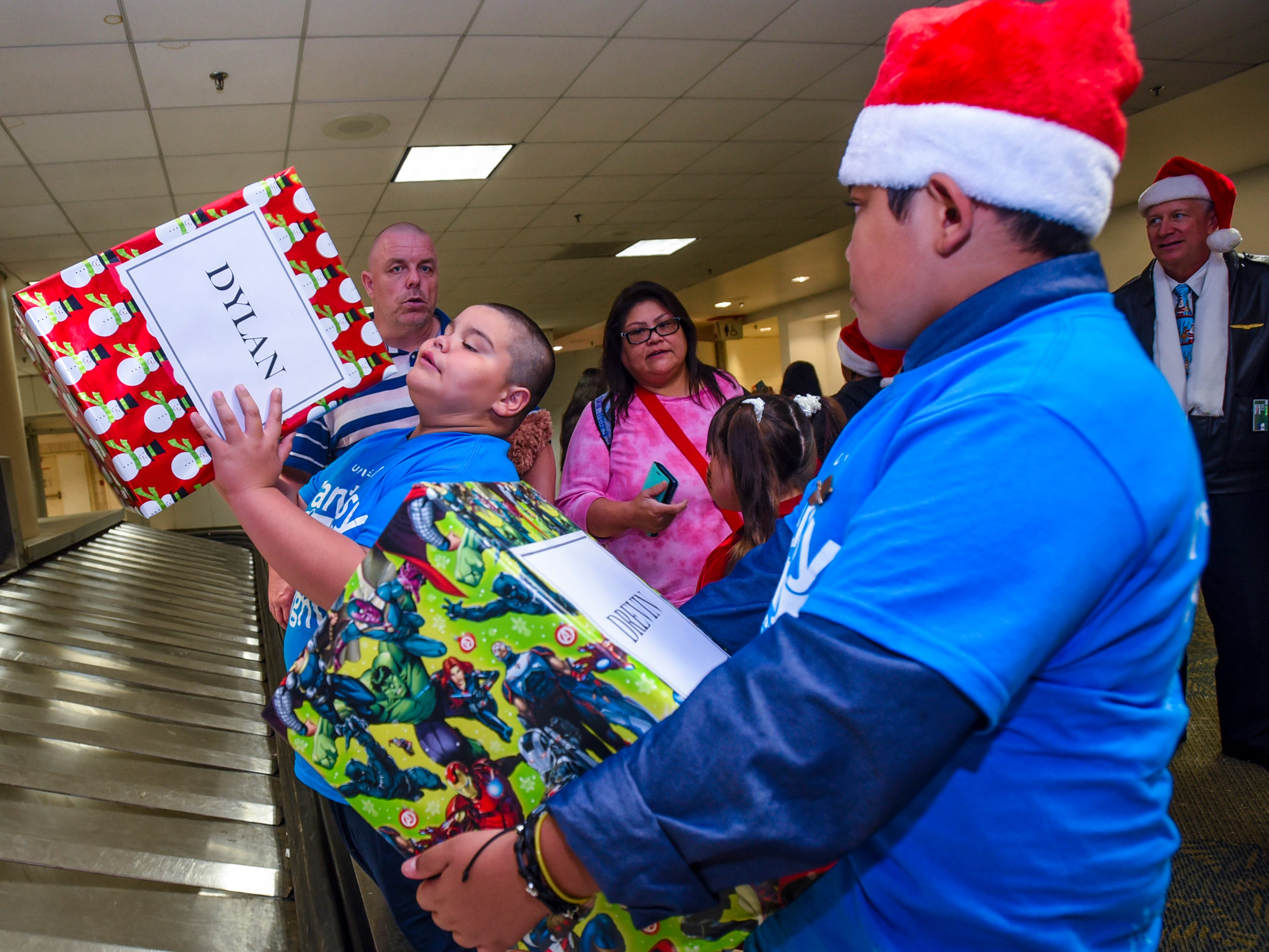 Dylan Paul Stremmelaar, 9, finds his gift on the luggage carousel after participating in United Airlines' Fantasy Flight to the North Pole at the A.B. Won Pat International Airport on Friday, Dec. 7, 2018. Thirty-three Guam Special Olympians, and their guests, were presented with an experience to enjoy live entertainment, food, games, holiday cookie decorating and face paintings after a make-believe flight to visit Santa Claus and his helpers. The event was the air carrier's fifth consecutive year of sharing holiday cheer with a group of the island's deserving children. This year, the airline's Guam hub was joined by 15 other United destinations around the globe in celebrating the holiday event.