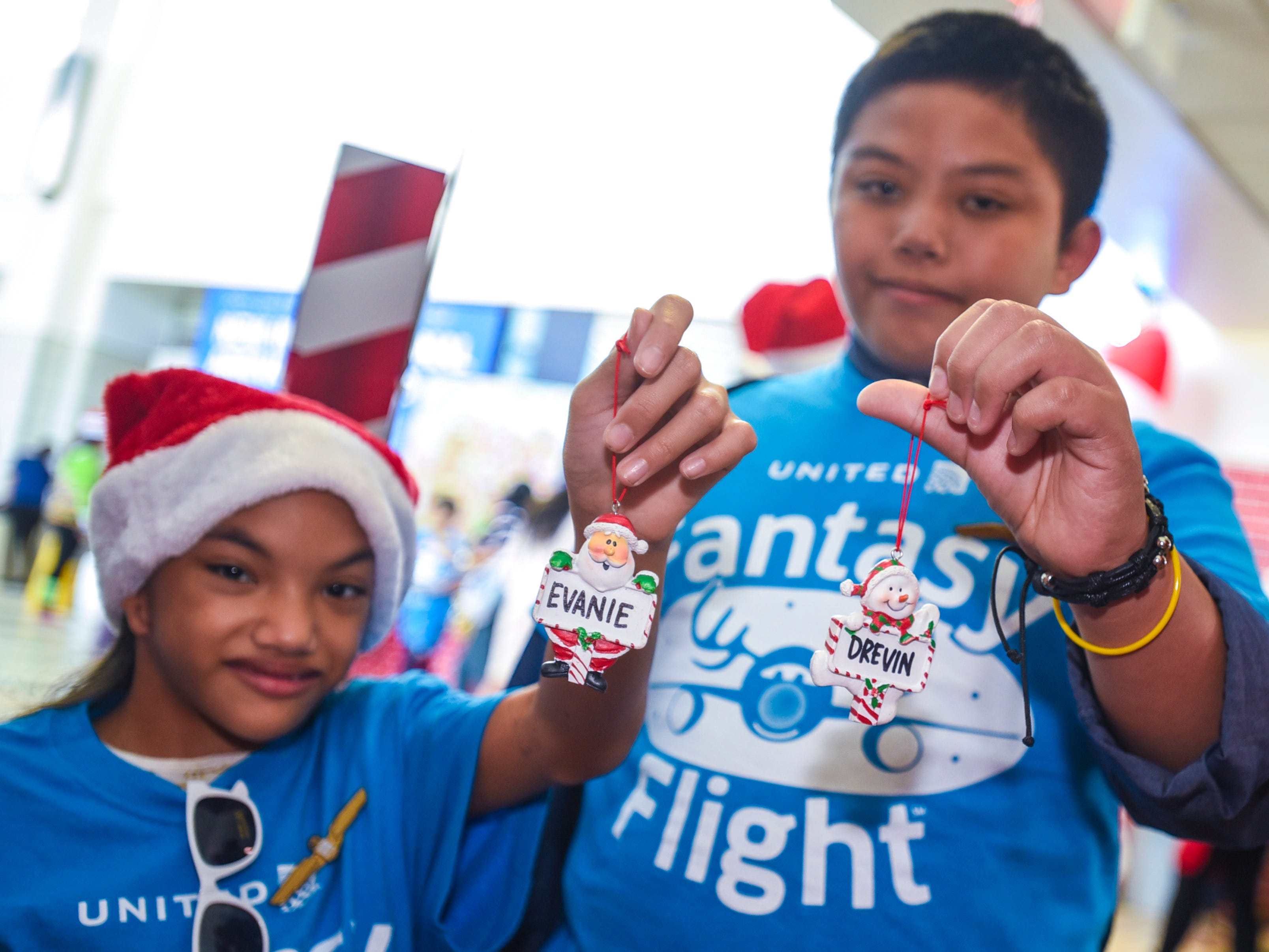 Siblings, Evanie and Drevin Blas, find personalized ornaments for them on a Christmas tree during United Airlines' Fantasy Flight to the North Pole at the A.B. Won Pat International Airport on Friday, Dec. 7, 2018. Thirty-three Guam Special Olympians, and their guests, were presented with an experience to enjoy live entertainment, food, games, holiday cookie decorating and face paintings after a make-believe flight to visit Santa Claus and his helpers. The event was the air carrier's fifth consecutive year of sharing holiday cheer with a group of the island's deserving children. This year, the airline's Guam hub was joined by 15 other United destinations around the globe in celebrating the holiday event.