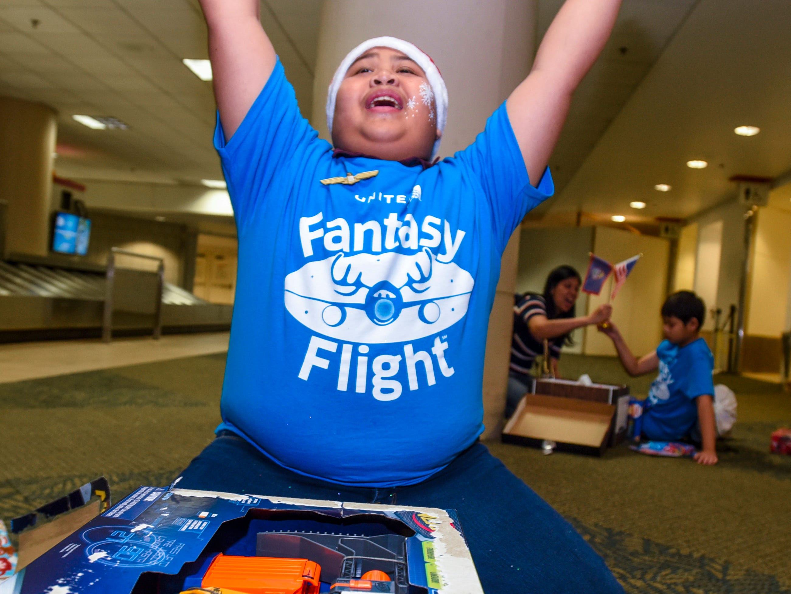 Jarod Joshua, 12, throws his arms up into the air in celebration after discovering the gift of a toy Nerf gun waiting for him on a luggage carousel during the finale of United Airlines' Fantasy Flight at the A.B. Won Pat International Airport on Friday, Dec. 7, 2018. Joshua and 32 other Guam Special Olympians were presented with an experience to enjoy live entertainment, food, games, holiday cookie decorating and face paintings after a make-believe flight to visit Santa Claus and his helpers. The event was the air carrier's fifth consecutive year of sharing holiday cheer with a group of the island's deserving children. This year, the airline's Guam hub was joined by 15 other United destinations around the globe in celebrating the holiday event.
