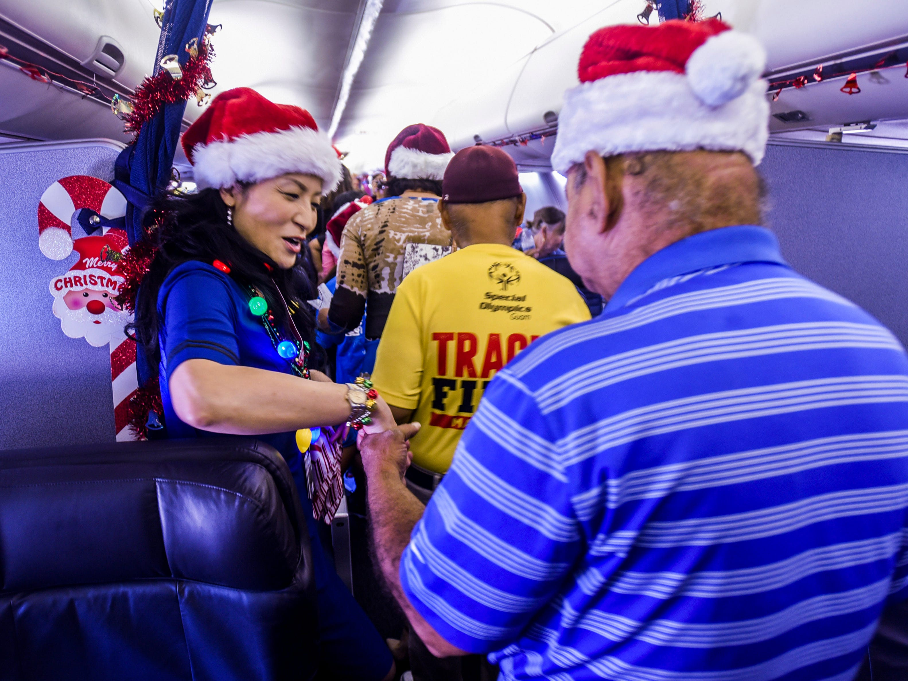 United Airline crew member, Yukiko Aricayos, greets a passenger as he boards United Airlines' Fantasy Flight to the North Pole at the A.B. Won Pat International Airport on Friday, Dec. 7, 2018. Thirty-three Guam Special Olympians, and their guests, were presented with an experience to enjoy live entertainment, food, games, holiday cookie decorating and face paintings after a make-believe flight to visit Santa Claus and his helpers. The event was the air carrier's fifth consecutive year of sharing holiday cheer with a group of the island's deserving children. This year, the airline's Guam hub was joined by 15 other United destinations around the globe in celebrating the holiday event.