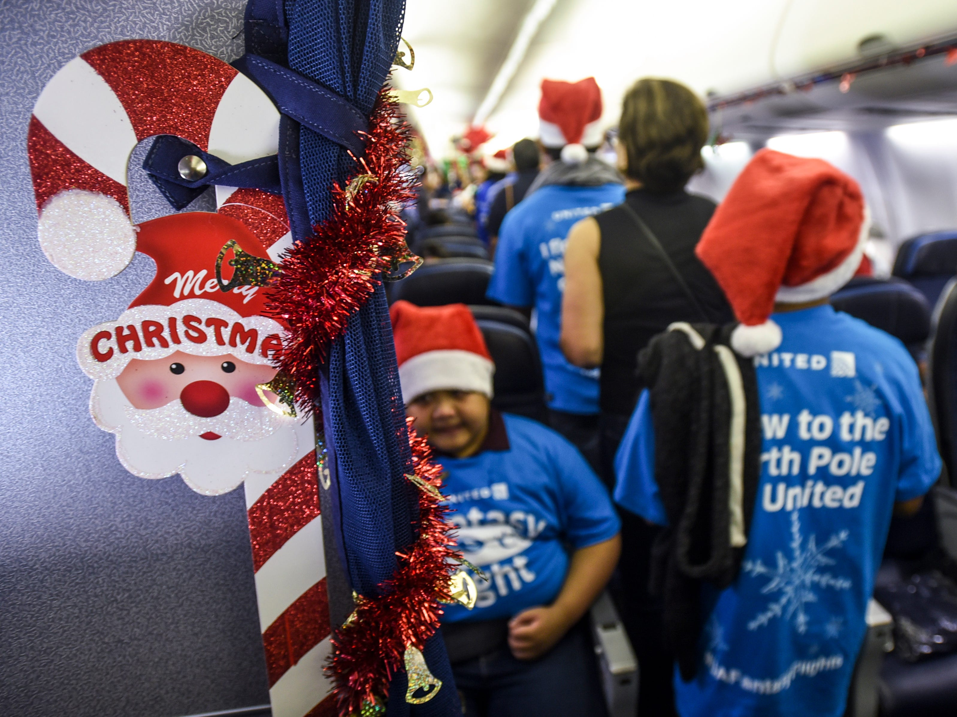 Passengers are assisted in locating their seats during United Airlines' Fantasy Flight to the North Pole at the A.B. Won Pat International Airport on Friday, Dec. 7, 2018. Thirty-three Guam Special Olympians, and their guests, were presented with an experience to enjoy live entertainment, food, games, holiday cookie decorating and face paintings after a make-believe flight to visit Santa Claus and his helpers. The event was the air carrier's fifth consecutive year of sharing holiday cheer with a group of the island's deserving children. This year, the airline's Guam hub was joined by 15 other United destinations around the globe in celebrating the holiday event.