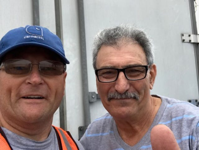 "Henderson City Manager Buzzy Newman grabs a ""selfie"" with the Central American trucker who brought his rig filled with disaster relief supplies to St. Andrews Church in Panama City, Fla."