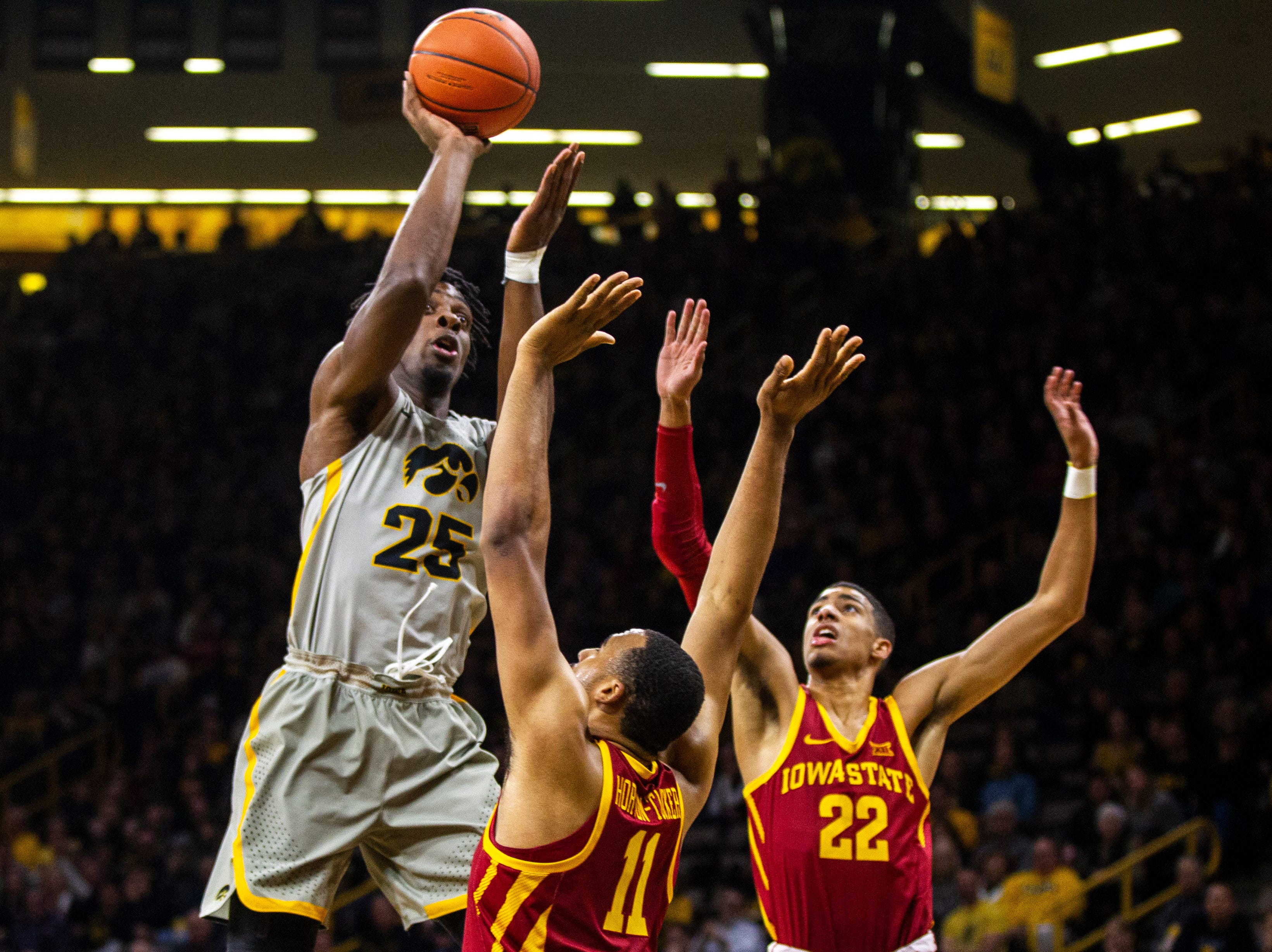Iowa forward Tyler Cook (25) attempts a basket while being defended by Iowa State guard Talen Horton-Tucker (11) and Iowa State guard Tyrese Haliburton (22) during a NCAA Cy-Hawk series men's basketball game on Thursday, Dec. 6, 2018, at Carver-Hawkeye Arena in Iowa City.