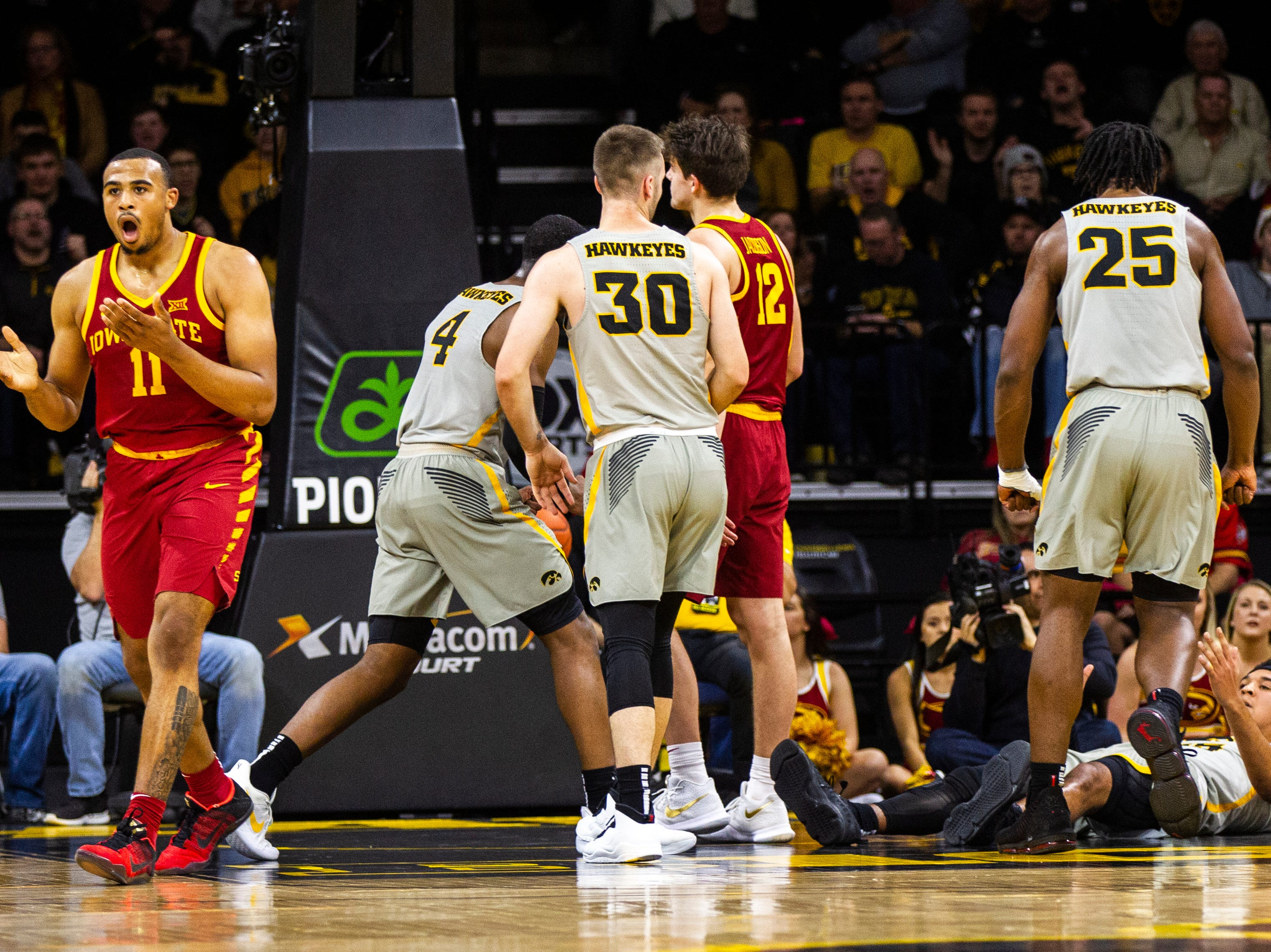 Iowa State guard Talen Horton-Tucker (11) reacts to a foul while Iowa forward Tyler Cook (25) helps up Iowa forward Cordell Pemsl (35) during a NCAA Cy-Hawk series men's basketball game on Thursday, Dec. 6, 2018, at Carver-Hawkeye Arena in Iowa City.