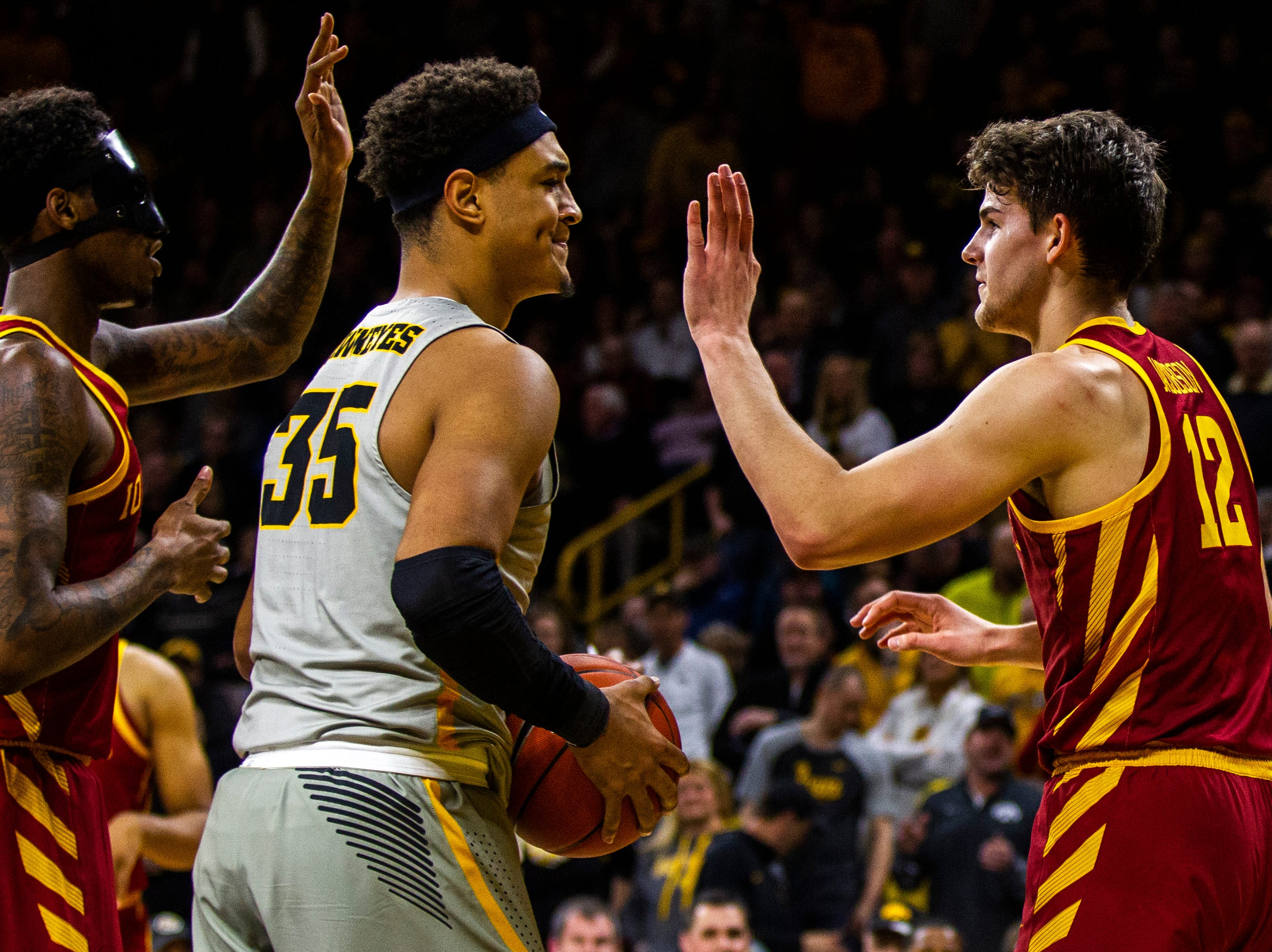 Iowa forward Cordell Pemsl (35) reacts after getting called for a foul while Iowa State forward Zoran Talley Jr. (left) high-fives Iowa State forward Michael Jacobson (12) during a NCAA Cy-Hawk series men's basketball game on Thursday, Dec. 6, 2018, at Carver-Hawkeye Arena in Iowa City.