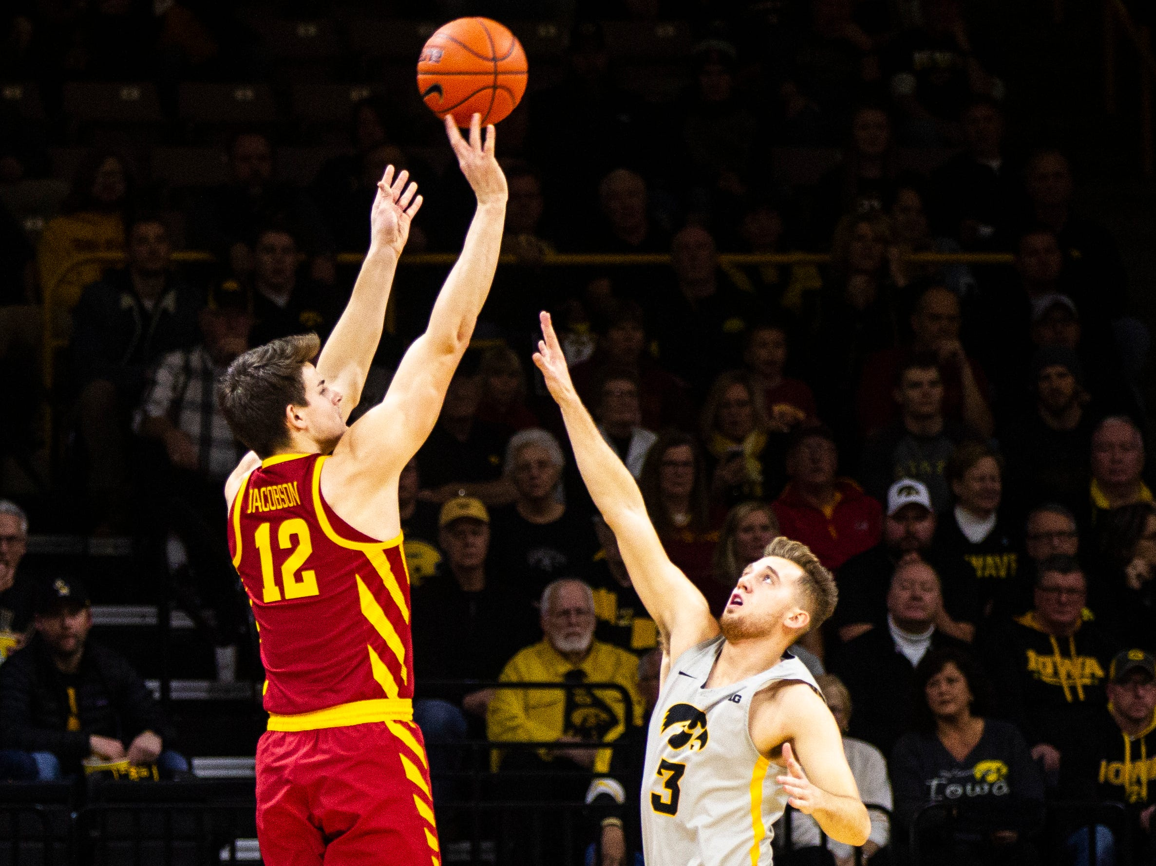 Iowa State forward Michael Jacobson (12) shoots a 3-point basket over Iowa guard Jordan Bohannon (3) during a NCAA Cy-Hawk series men's basketball game on Thursday, Dec. 6, 2018, at Carver-Hawkeye Arena in Iowa City.