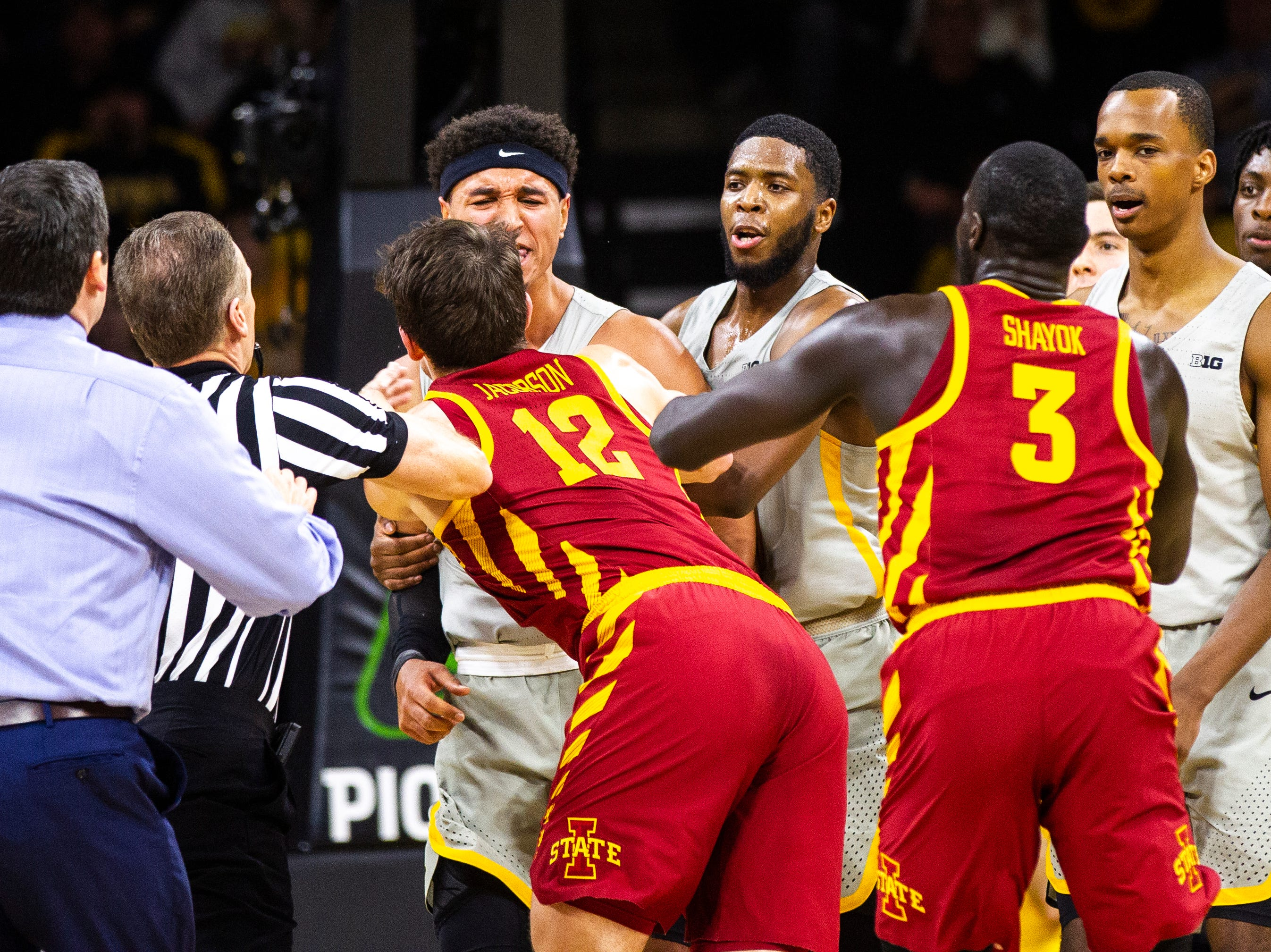 Iowa forward Cordell Pemsl (35) gets tangled up with Iowa State forward Michael Jacobson (12) while Iowa State head coach Steve Prohm (far left) runs in during a NCAA Cy-Hawk series men's basketball game on Thursday, Dec. 6, 2018, at Carver-Hawkeye Arena in Iowa City.