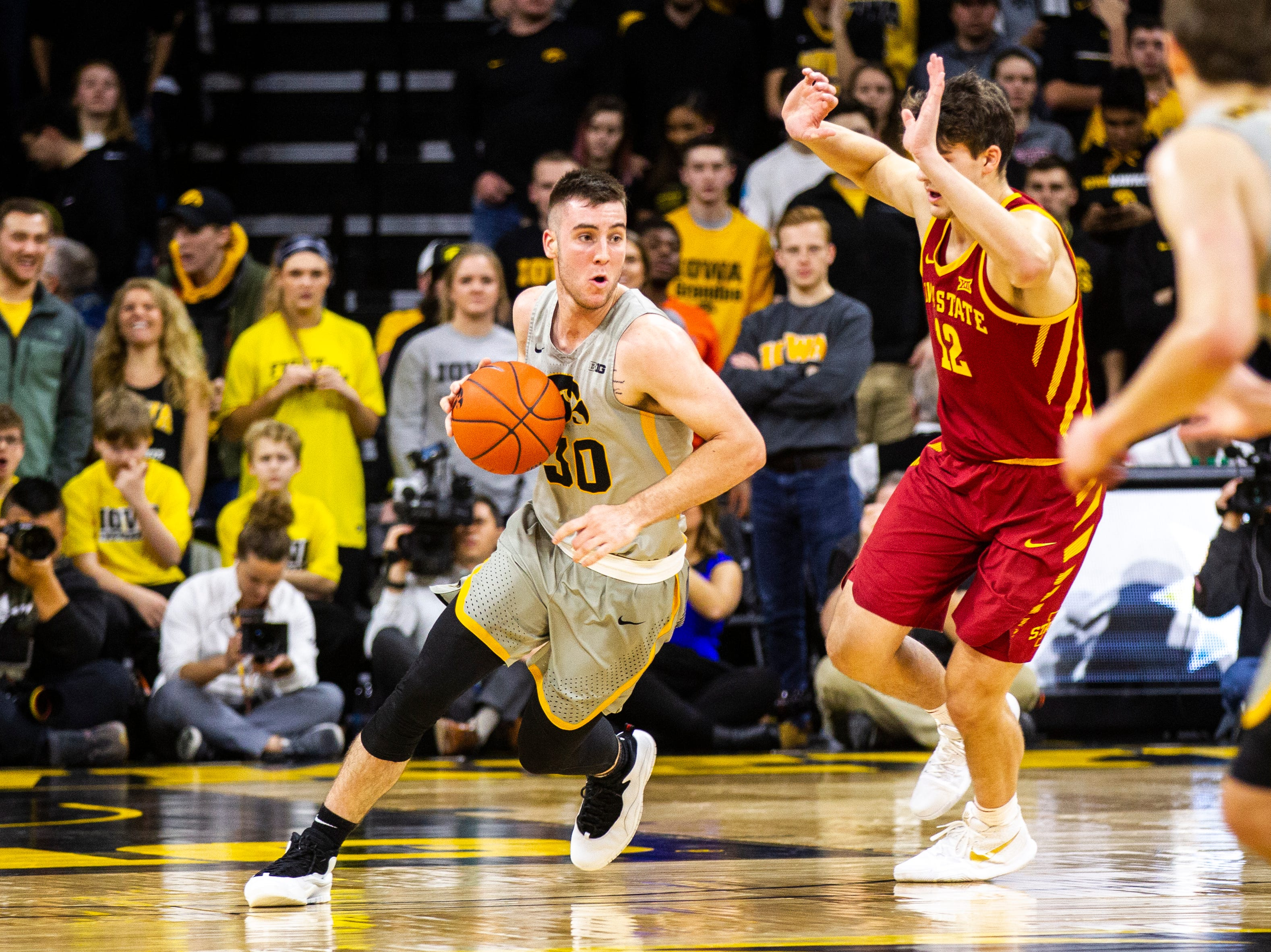 Iowa guard Connor McCaffery (30) takes the ball up court while being defended by Iowa State forward Michael Jacobson (12) during a NCAA Cy-Hawk series men's basketball game on Thursday, Dec. 6, 2018, at Carver-Hawkeye Arena in Iowa City.