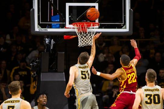 Iowa forward Nicholas Baer tips a ball in the hoop Thursday against Iowa State.