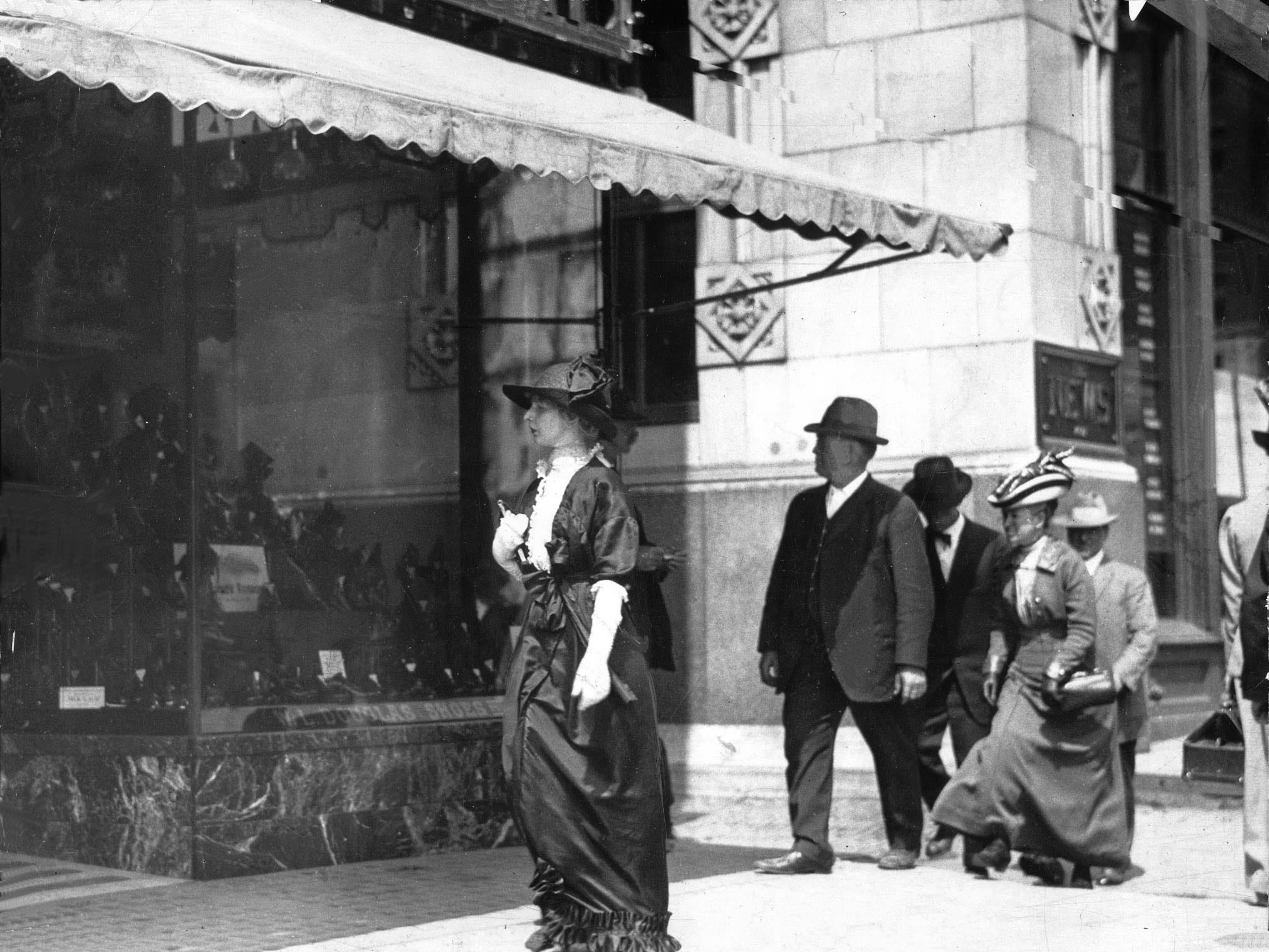"Dark suits, long dresses and fancy hats were the style of the day when this photo was taken in Downtown Indianapolis circa 1914. Pedestrians are shown walking west along the north side of Washington Street, crossing Bird Street, a north-south street located between Illinois and Meridian streets. At left is a store in the Griffith Block at 34 W. Washington St., featuring a window display of shoes and a ""W. L. Douglas Shoes"" sign. The Indianapolis News Building, built in 1910 at 30W. Washington St., is seen in the background, across Bird Street."