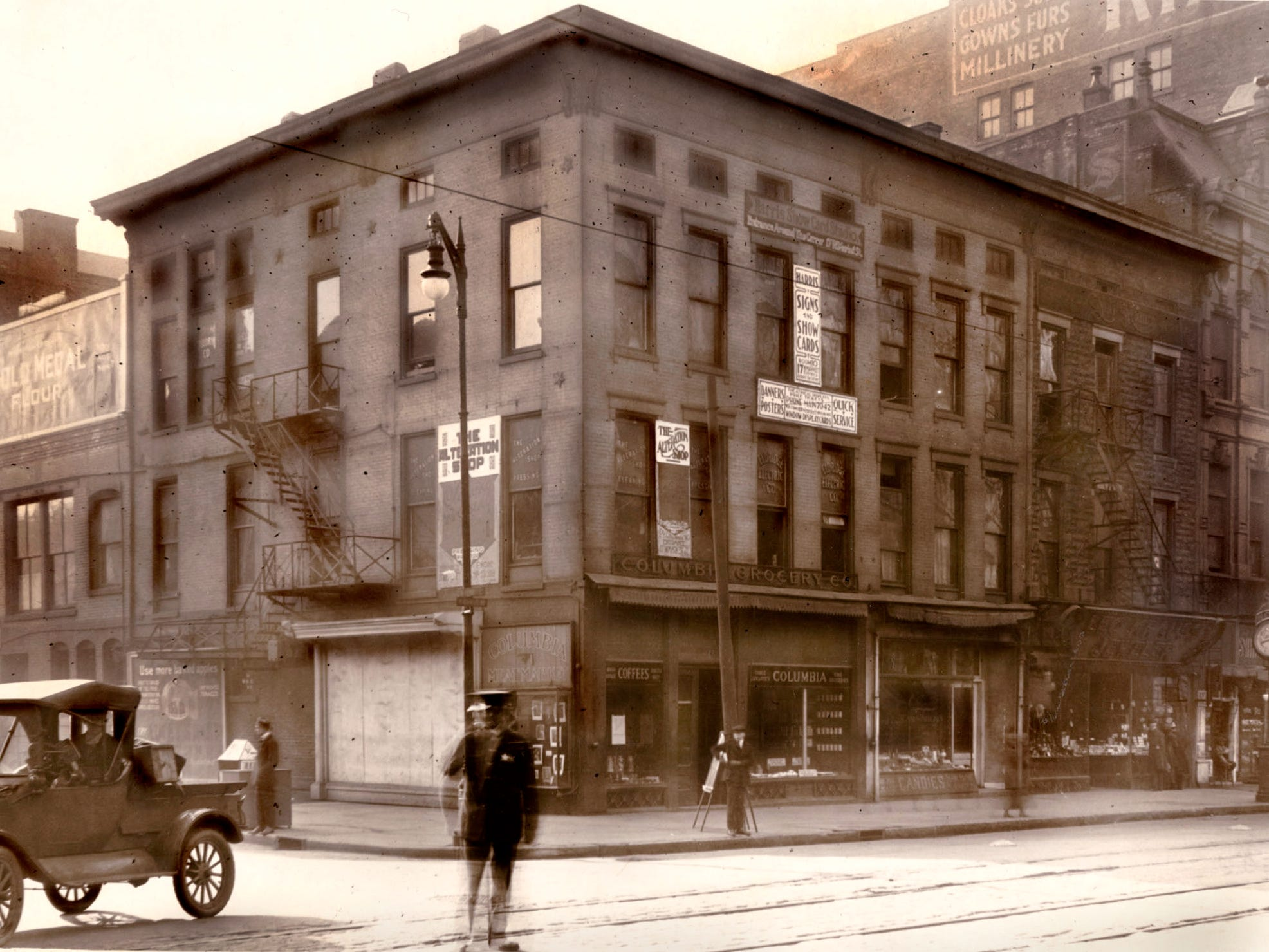 A policeman directs traffic in the intersection of Market and Illinois Streets on April 13, 1919 in this photo looking southeast (Illinois Street is at right). At the time, the Columbia Grocery Co. occupied the corner ground floor space. To the right of the grocery was the Olympia Candy Store and Leo Krauss Jewelry. Businesses on upper floors included The Alteration Shop, Eldridge Electric Co. and Harris Show Signs and Show Cards, which produced banners, posters and window display cards. The building is no longer standing, and the site is currently occupied by The Illinois Building at 17 W. Market St.