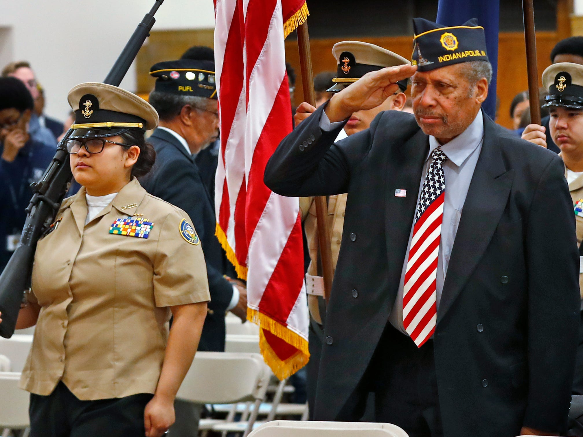 American Legion members salute as the colors are posted by the Pike High School's Junior Reserve Officer Training Corps Color Guard, during the Pearl Harbor Day Remembrance at Riverside High School, Friday, Dec. 7, 2018.  The former Heslar Naval Armory used to host the event to remember those who died and to honor those who survived in the Dec. 7, 1941 Japanese attack on Pearl Harbor which plunged the United States into World War II.