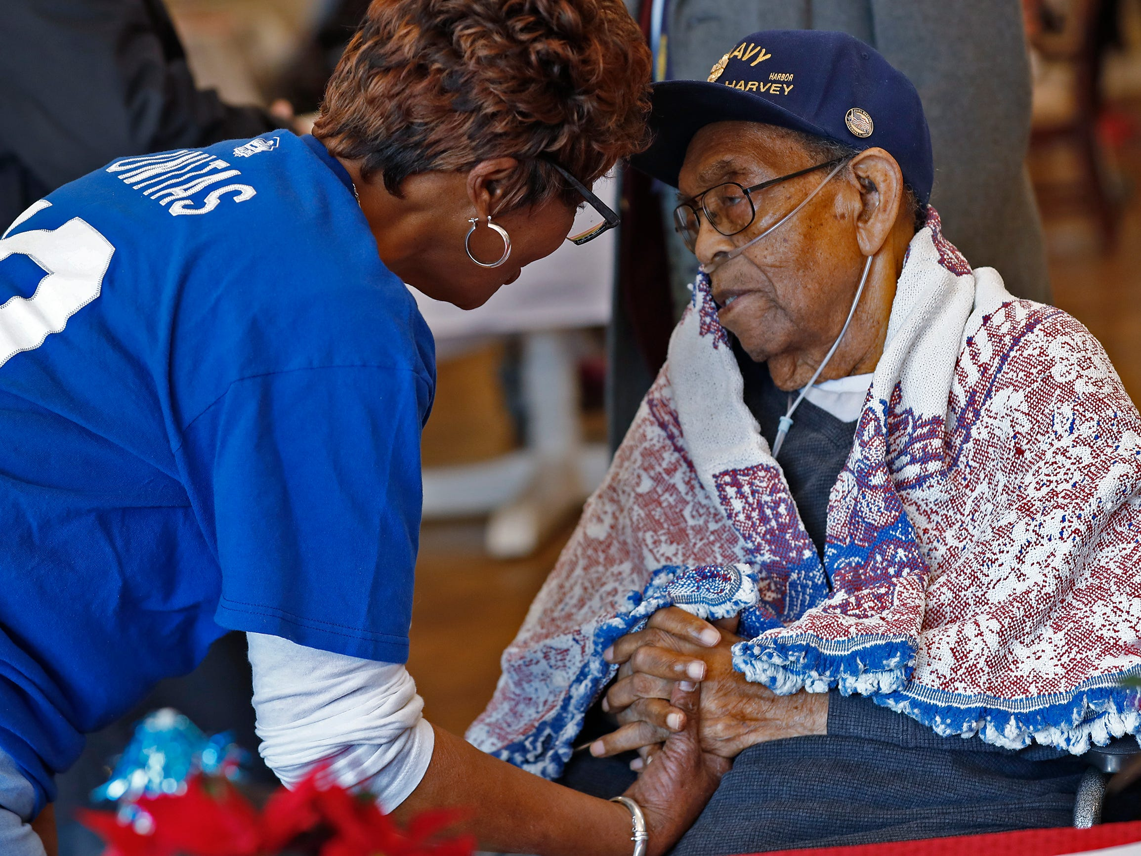 Pearl Harbor attack survivor William Harvey, right, speaks to CNA Lolita Ellis at the Alpha Home where Harvey lives, Friday, Dec. 7, 2018.  Harvey was unable to attend a Pearl Harbor Day Remembrance at Riverside High School, so several members with The American Legion came to visit him.  The former Heslar Naval Armory, now Riverside High School, used to host the event to remember those who died and to honor those who survived in the Dec. 7, 1941 Japanese attack on Pearl Harbor which plunged the United States into World War II.  This year, the event was brought back.  There was also a 21-gun salute, taps played, and a wreath tossing ceremony on the banks of the White River adjacent to the school.