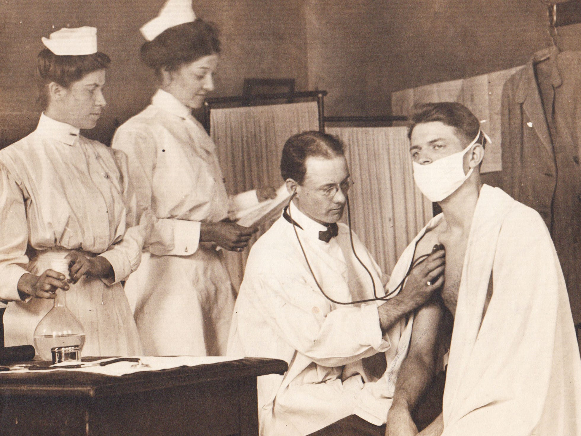 Dr. F. E. Jackson makes an examination of a patient at the City Dispensary as Mary McCoy (left) and Blanche Neff, nurses from the tuberculosis clinic visit assist.  1910 file photo