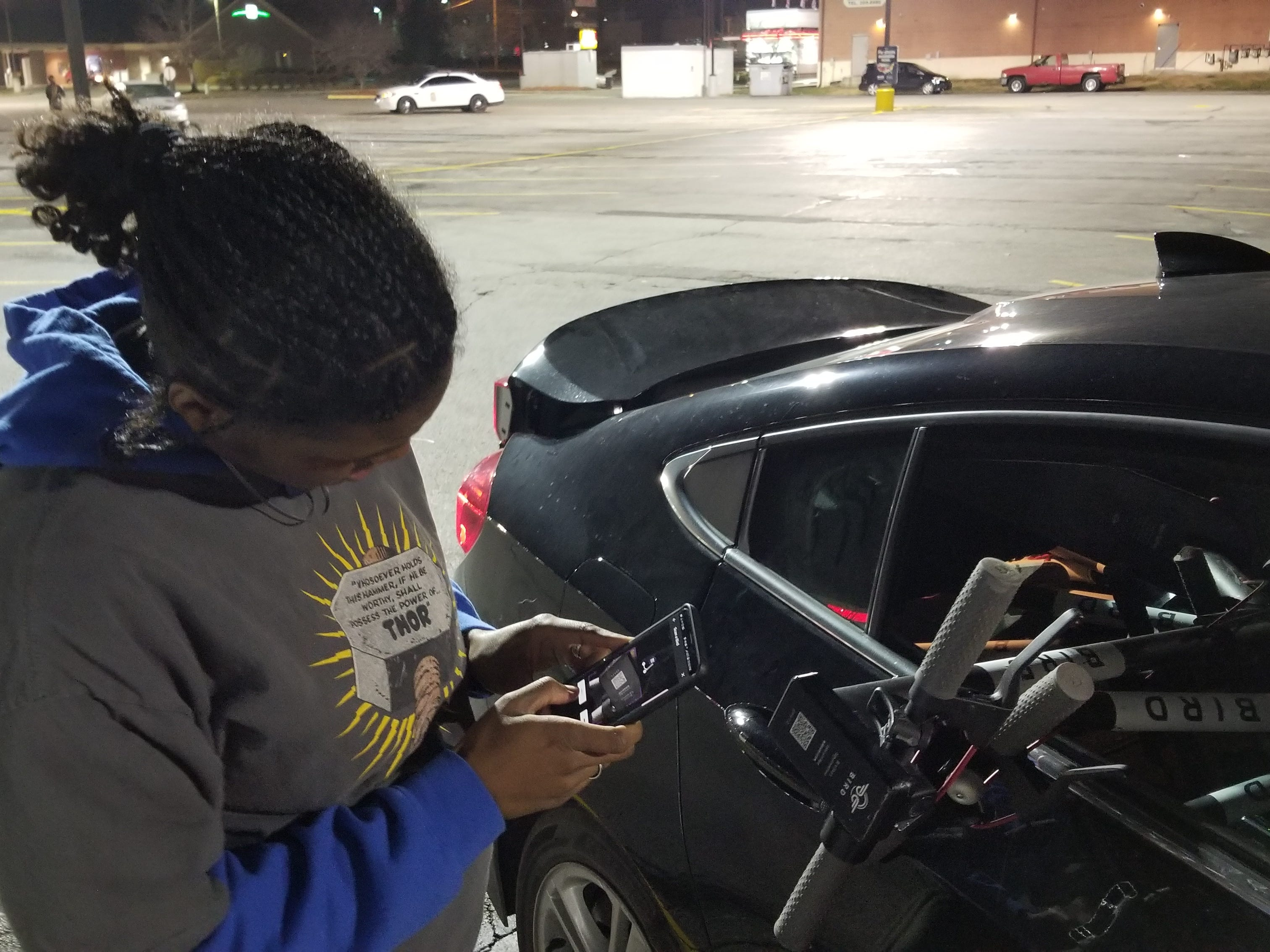 Simone Thomas scans a Bird scooter on Nov. 21, 2018, in Indianapolis.