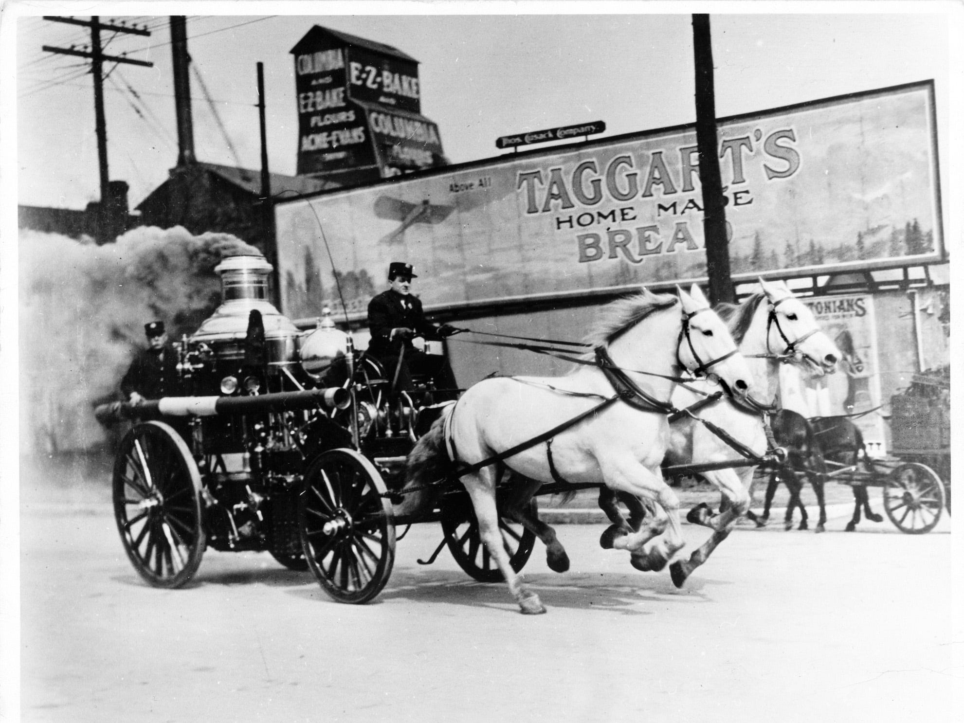 Firefighter Charles Gregory (right) drove one of the Indianapolis Fire DepartmentÕs Ahrens steam engines, housed at the old No. 6 station, on a simulated fire run down West Washington Street near Blackford Street in 1911. Riding in the back was engineer John Stake. The photograph appeared in the April 22, 1911 edition of The Indianapolis News, accompanying a poem titled, ÔÔWhen the SixÕs Grays Are Out.ÕÕ