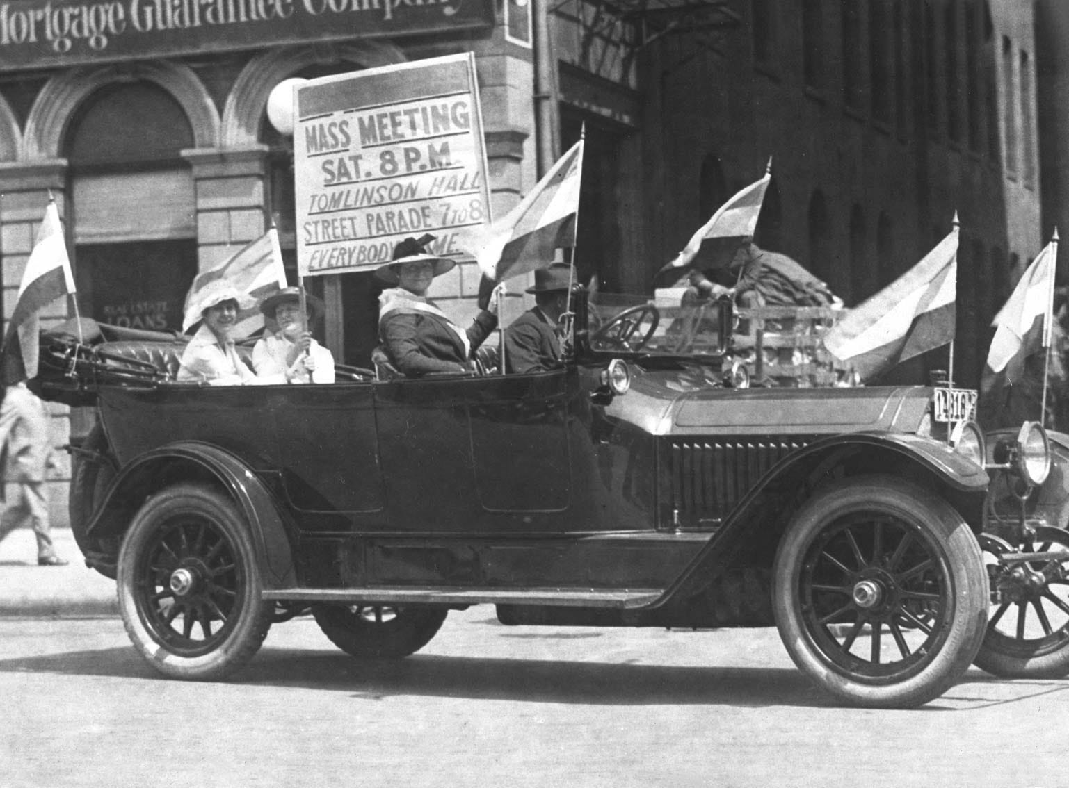Decorated automobiles drove throughout the city on June 23, 1916, announcing a mass meeting the next night, to further the cause of suffrage (womenÕs right to vote). This automobile, owned by Republican nominee for vice-president, Charles W. Fairbanks, led the procession. Fairbanks' daughter, Mrs. John W. Timmons, sitting in the front seat, held up the sign with Elsie Hill and Corinne Eaglesfield (in the back seat). The next afternoon, the Indiana branch of the Congressional Union was organized, followed later in the day by IndianapolisÕ first suffrage parade.