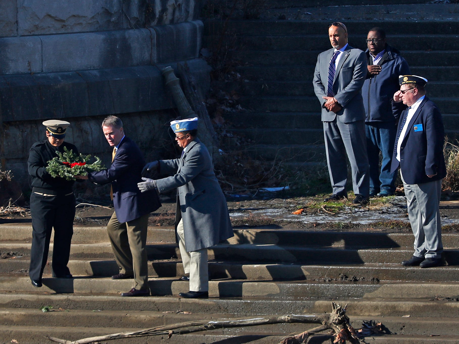 Valeria Hernandez, left, with Pike High School's JROTC, helps Mayor Joe Hogsett to the White River banks for a wreath tossing ceremony, as part of the Pearl Harbor Day Remembrance at Riverside High School, Friday, Dec. 7, 2018.  The former Heslar Naval Armory used to host the event to remember those who died and to honor those who survived in the Dec. 7, 1941 Japanese attack on Pearl Harbor which plunged the United States into World War II.