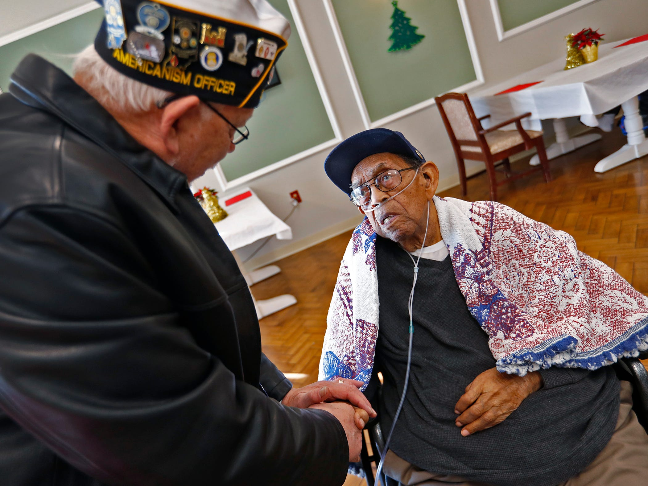 American Legion's 11th District Commander Rees Morgan, left, speaks with Pearl Harbor attack survivor William Harvey, right, at the Alpha Home where he lives, Friday, Dec. 7, 2018.  Harvey was unable to attend a Pearl Harbor Day Remembrance at Riverside High School, so several members with The American Legion came to visit him.  The former Heslar Naval Armory, now Riverside High School, used to host the event to remember those who died and to honor those who survived in the Dec. 7, 1941 Japanese attack on Pearl Harbor which plunged the United States into World War II.  This year, the event was brought back.  There was also a 21-gun salute, taps played, and a wreath tossing ceremony on the banks of the White River adjacent to the school.