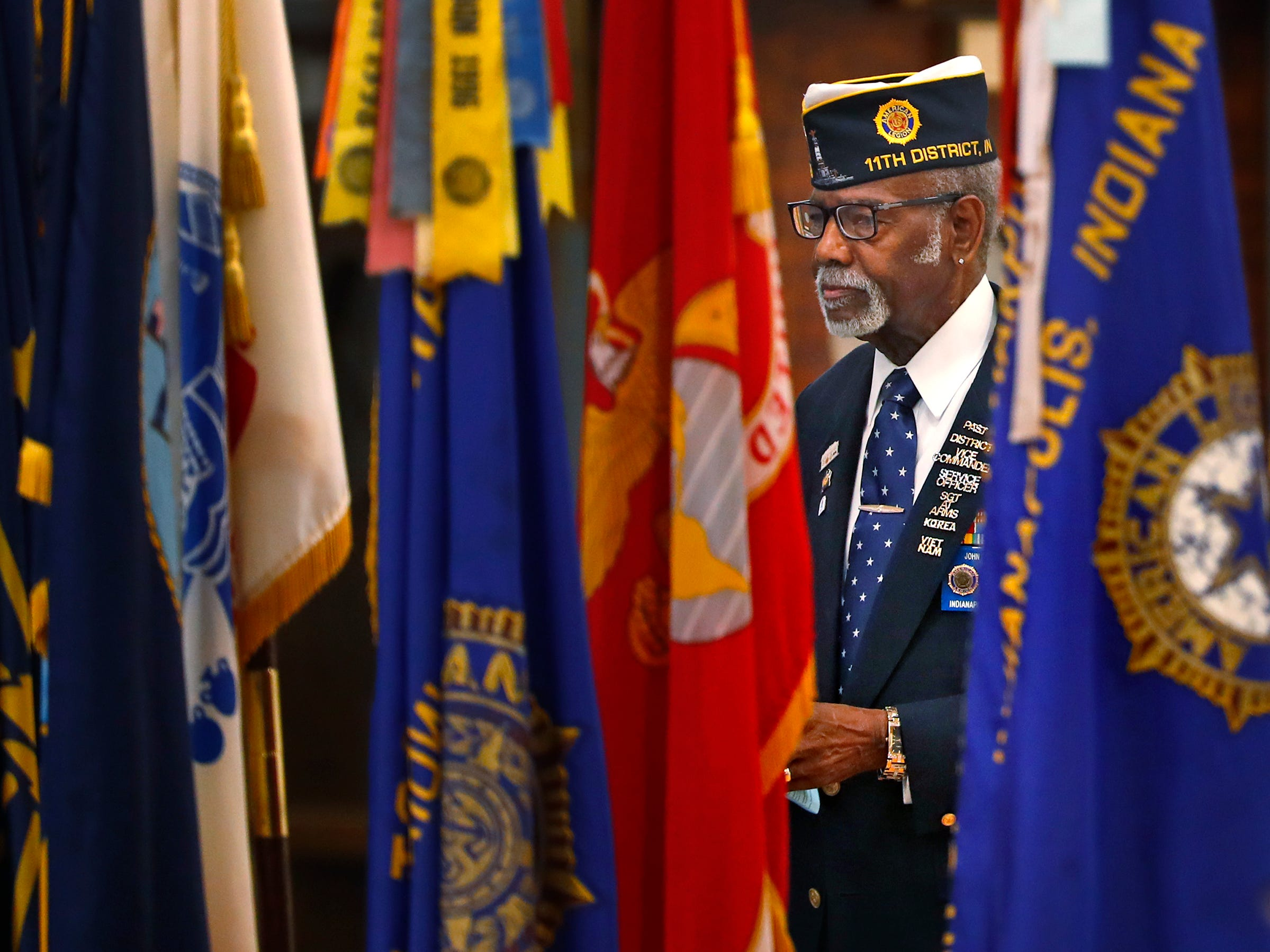 American Legion Post 249's John Thomas watches through flags, during the Pearl Harbor Day Remembrance at Riverside High School, Friday, Dec. 7, 2018.  The former Heslar Naval Armory used to host the event to remember those who died and to honor those who survived in the Dec. 7, 1941 Japanese attack on Pearl Harbor which plunged the United States into World War II.