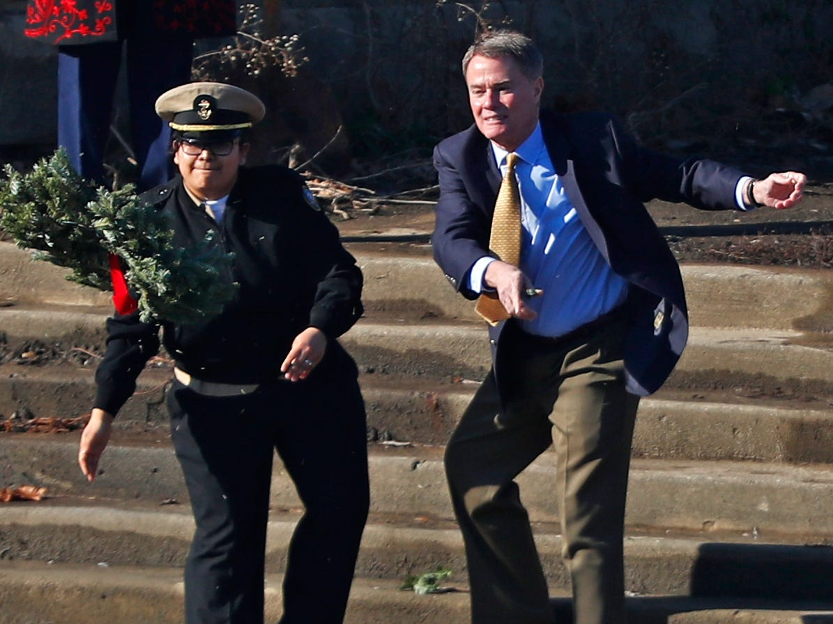 Valeria Hernandez, left, with Pike High School's JROTC, and Mayor Joe Hogsett toss a wreath into the White River, as part of the Pearl Harbor Day Remembrance at Riverside High School, Friday, Dec. 7, 2018.  The former Heslar Naval Armory used to host the event to remember those who died and to honor those who survived in the Dec. 7, 1941 Japanese attack on Pearl Harbor which plunged the United States into World War II.