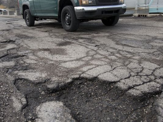 A pothole threatens a car on Westfield Road in the Broad Ripple section of Indianapolis.