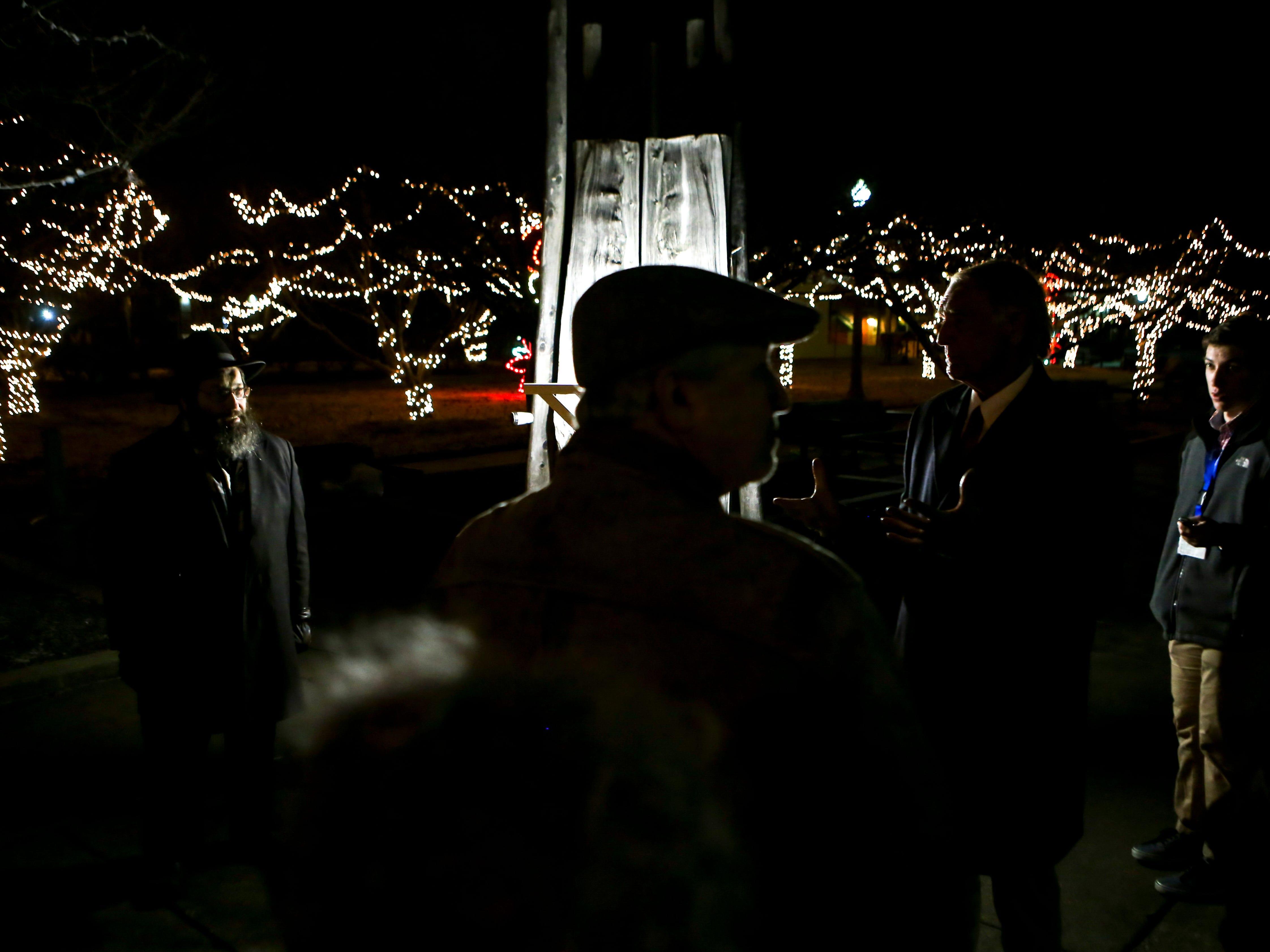 Visits gather around the lit menorah display during the first public Chanukah Menorah Lighting at Anderson Park in Jackson, Tenn., on Thursday, Dec. 6, 2018.