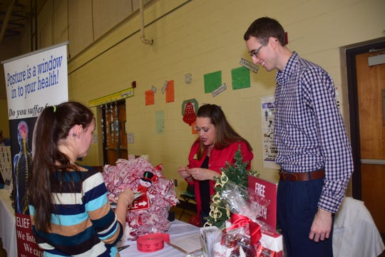 Cretia Goodin, left, signs up to win a Christmas Wreath with Alaina Vandermark and Dr. Zackery Harper of Southeast Precision Clinic of Chiropractic at the Christmas in Karns vender fair held at Karns Elementary School Saturday, Dec. 1.