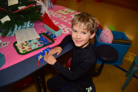 Derrick Billman, 6, makes a bookmark at a craft station sponsored by Sew Fine Studio at the Christmas in Karns vender fair held at Karns Elementary School Saturday, Dec. 1.