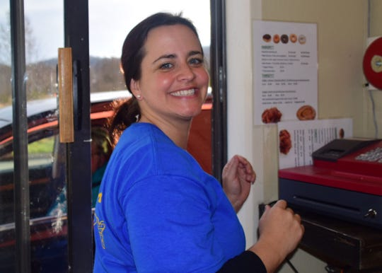 Co-owner Mellisa Wells serves customers at the drive-thru window at Beaver's Dough Joe on Wednesday, Dec. 5.