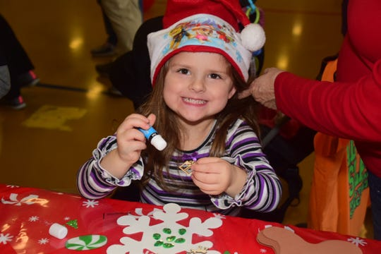 Laylah Bonney, 4, makes bejeweled snowflakes at a booth sponsored by Karns High School JrROTC at the Christmas in Karns vendor fair.