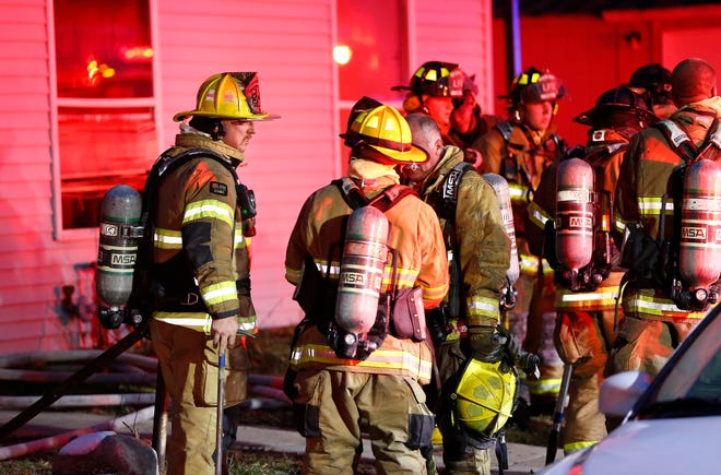 Firefighters assemble on the sidewalk after quickly knocking down a fire in a home in the 1200 block of Cincinnati Street Friday, December 7, 2018, in Lafayette.
