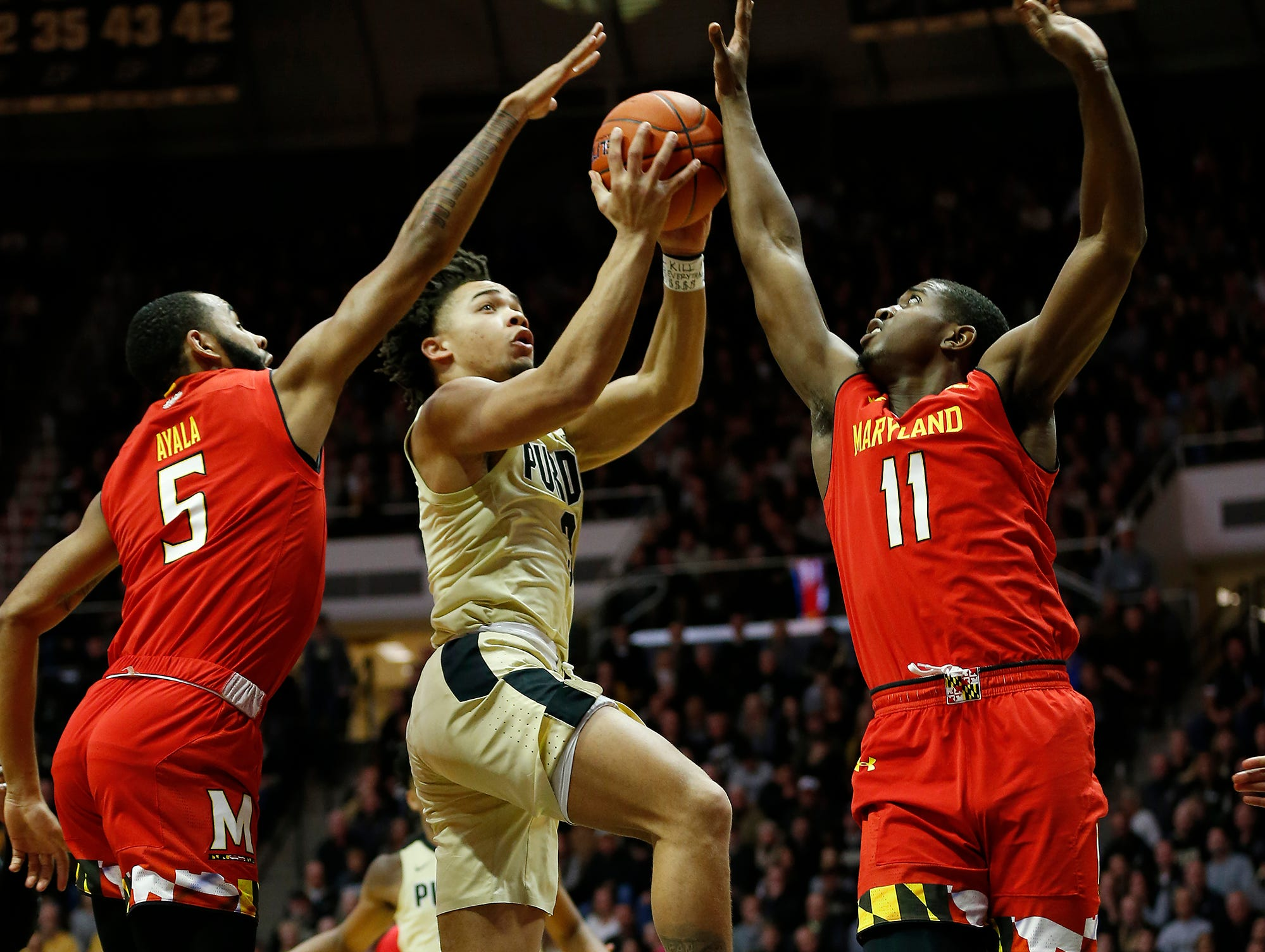 Carsen Edwards of Purdue drives between Eric Ayala and Darryl Morsell of Maryland for a shot Thursday, December 6, 2018, at Mackey Arena.