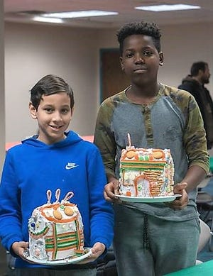 Christopher Ransom and Jaden Smith show off their finished gingerbread house at the Main Library. Upcoming gingerbread house programs are scheduled at theButler, Lucas and Ontario branches.