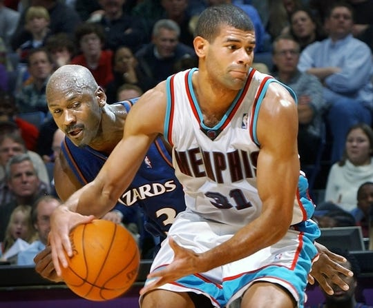 Washington Wizards' Michael Jordan keeps his eye on the ball as Memphis Grizzlies' Shane Battier dribbles during a game at the Pyramid Arena in 2002.