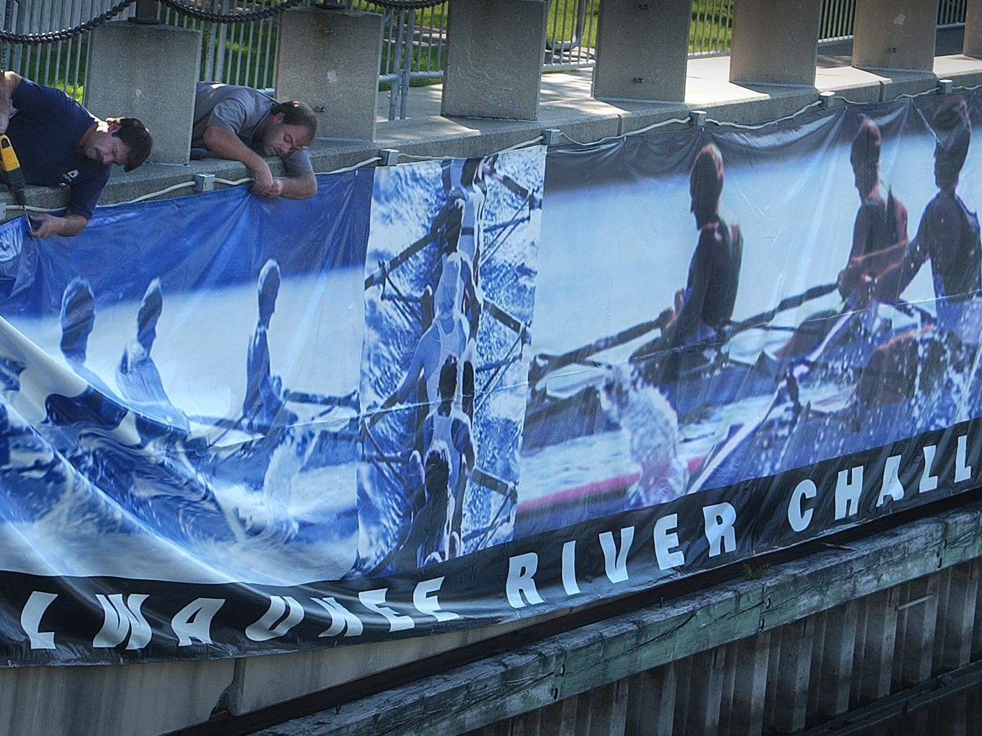Marcus Center for the performing arts employees Rick Larson, left, and Mike Weber hang a giant banner behind the center in preparation for the upcoming Milwaukee River Challenge Saturday, Sept. 21, 2002, a collegiate crew race along the Milwaukee River in downton Milwaukee. A field of over 400 rowers -- including teams from Marquette University and the University of Wisconsin -- is expected for the competition. The Milwaukee River Challenge is a two-way race, approximately 2.2 miles in each direction, on the Milwaukee River from Buffalo St. to Humboldt Ave. and back.