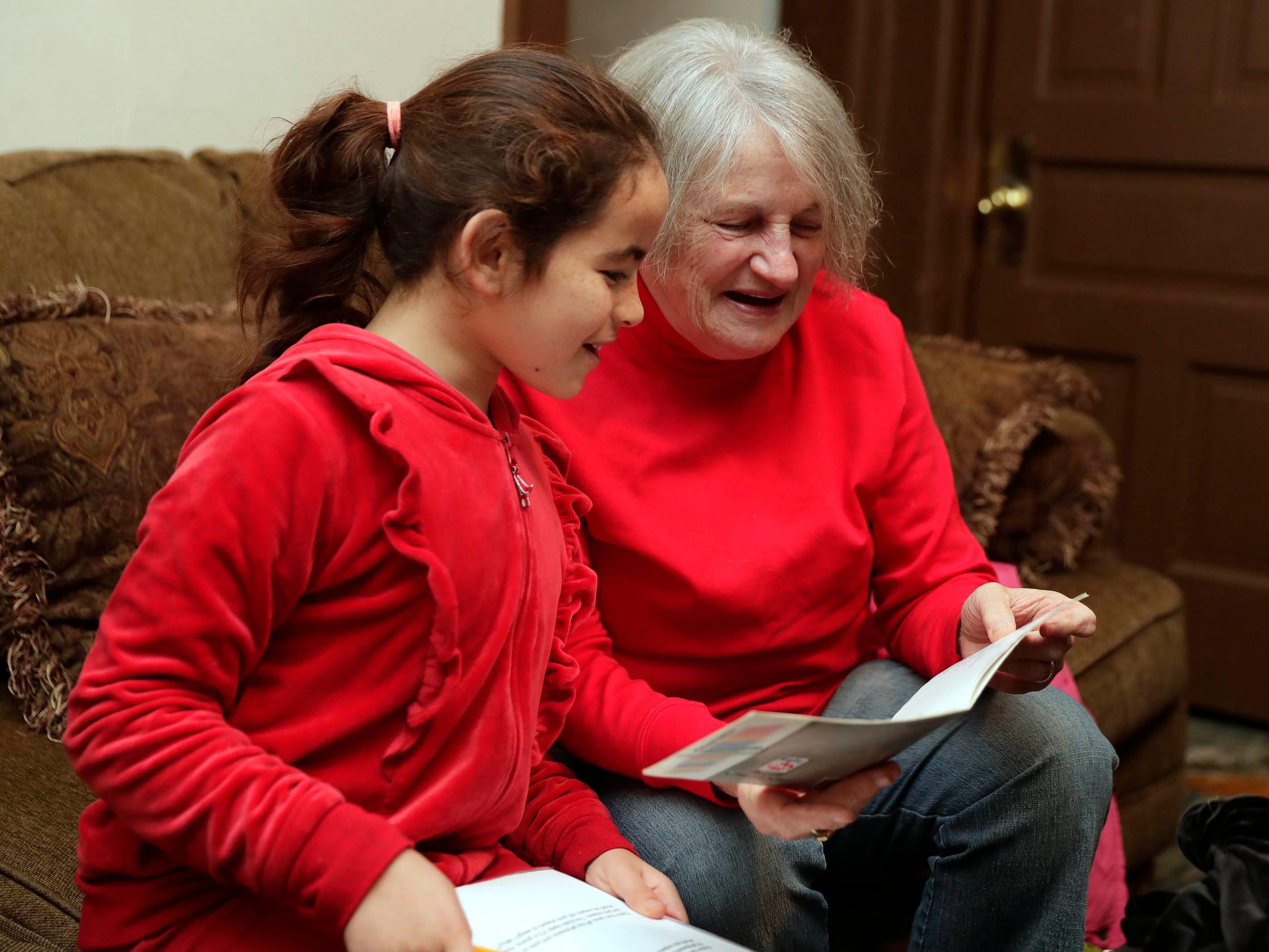 Nisrin Hamdoun, 11, gets help with her math from Mary Ward.