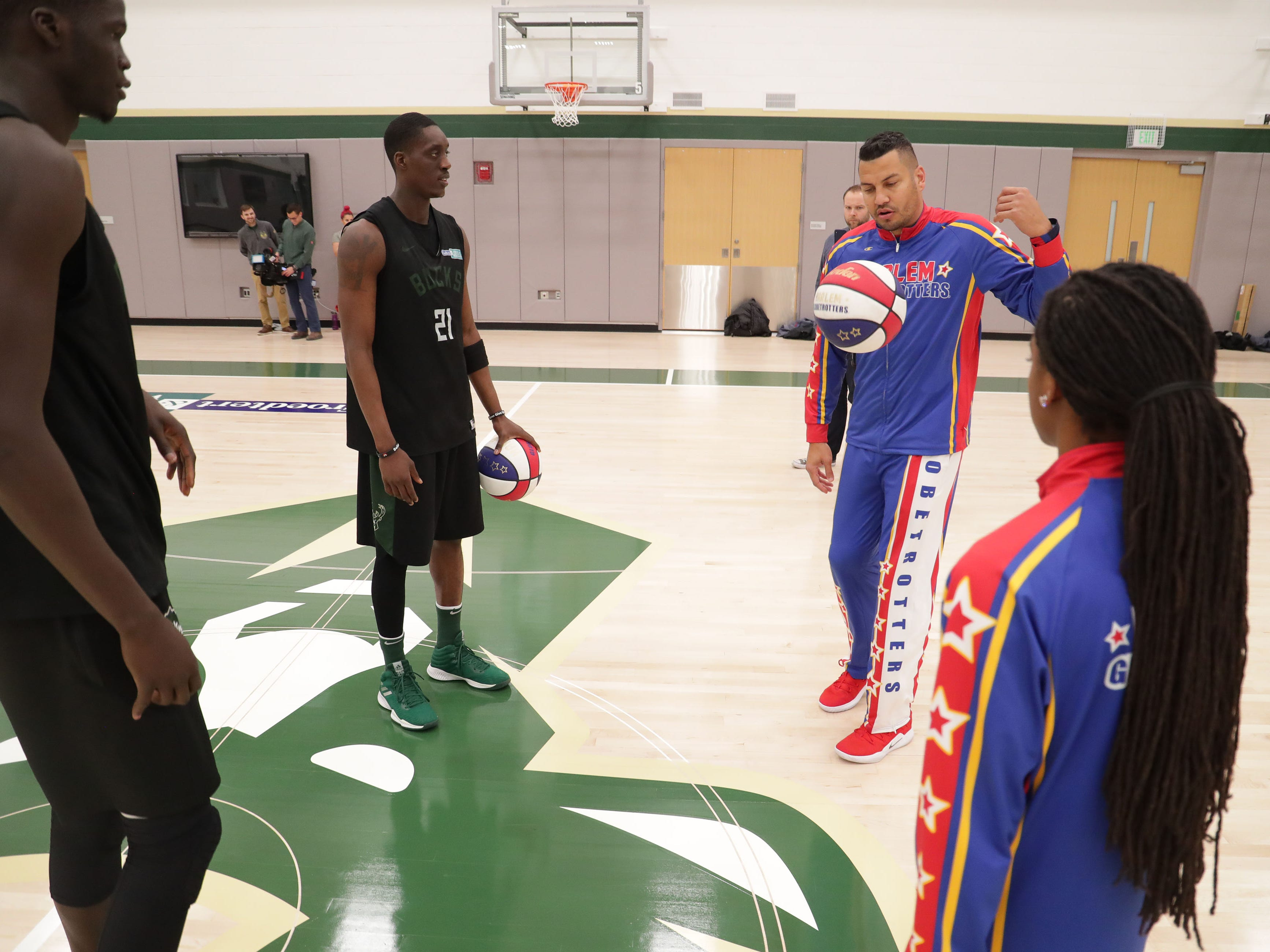 The Milwaukee Bucks' Thon Maker (left) and Tony Snell get a few pointers from the Harlem Globetrotters' Orlando El Gato Melendez and Lili Champ Thompson (far right).
