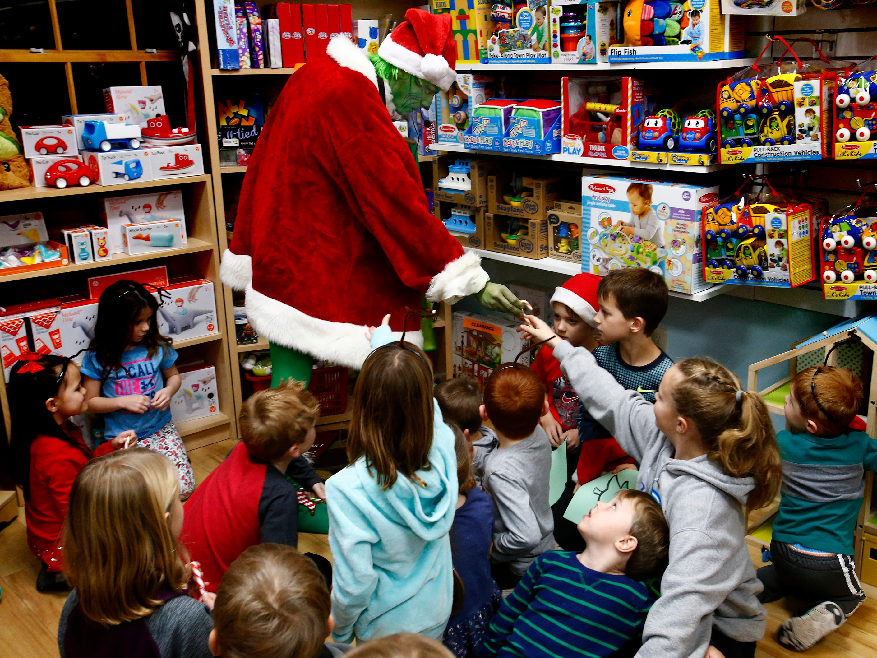 The Grinch, played by Rich Schoenholtz, hands out pickle, bacon and gravy-flavored candy canes before reading his favorite book to a packed store during Grinchmas in Pewaukee at Silly Willyz on Dec 6.