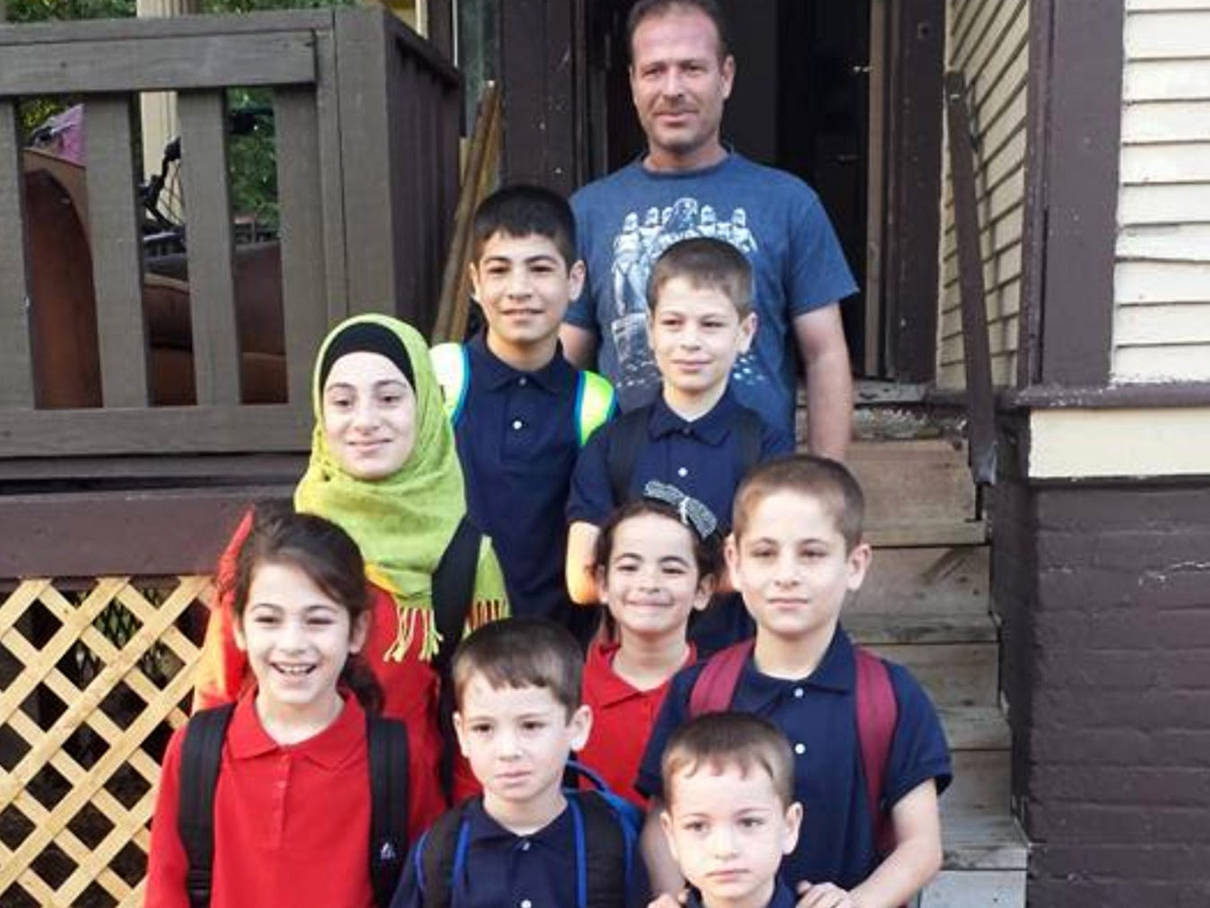 Turki Hamdoun (back) poses for a photo with eight of his eleven children at their south side home on the first day of school in the fall of 2017.