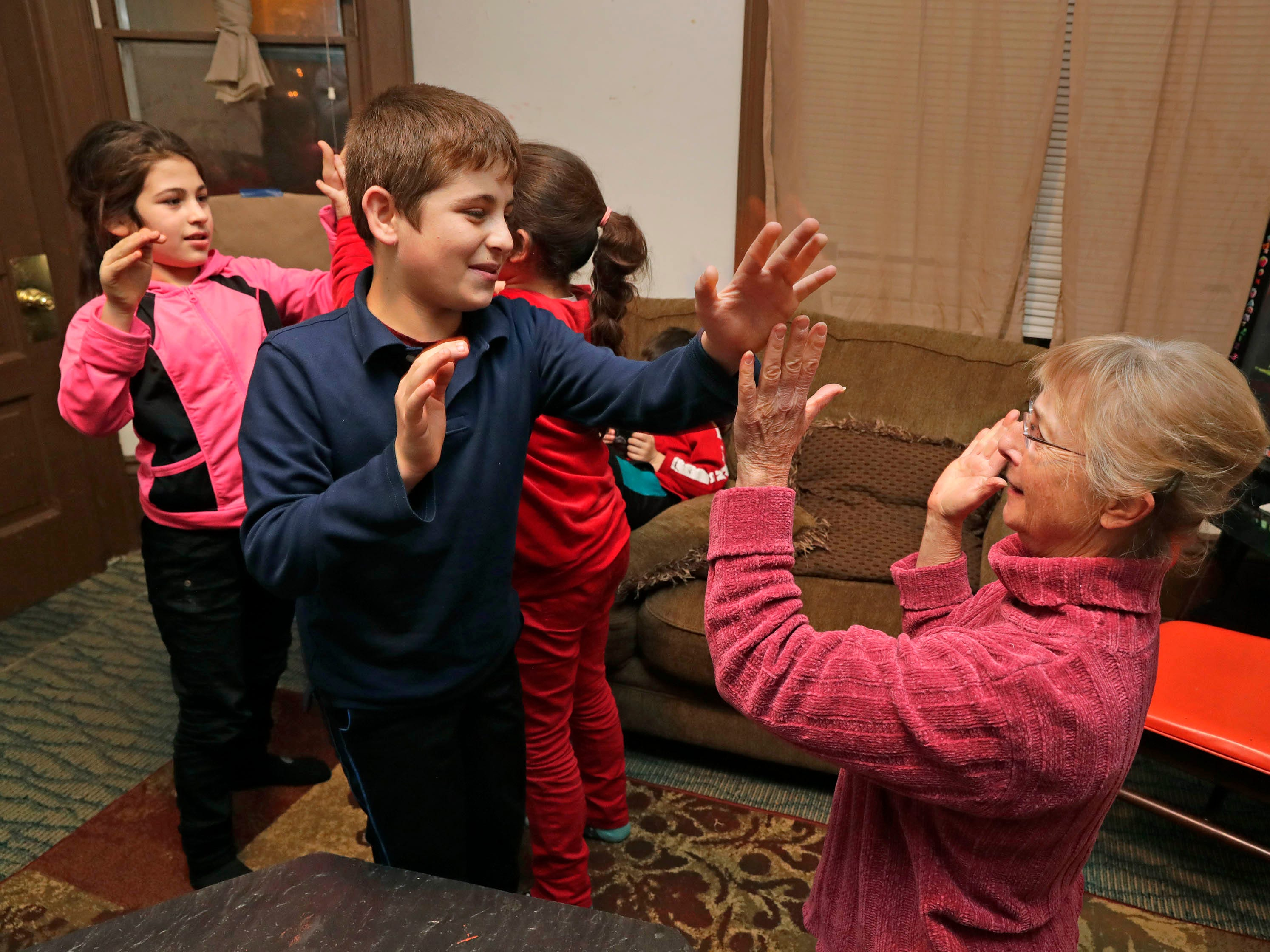 Carol Johnstone and Nizar Hamdoun, 11, play a clapping game at the Hamdoun family home on Milwaukee's south side.