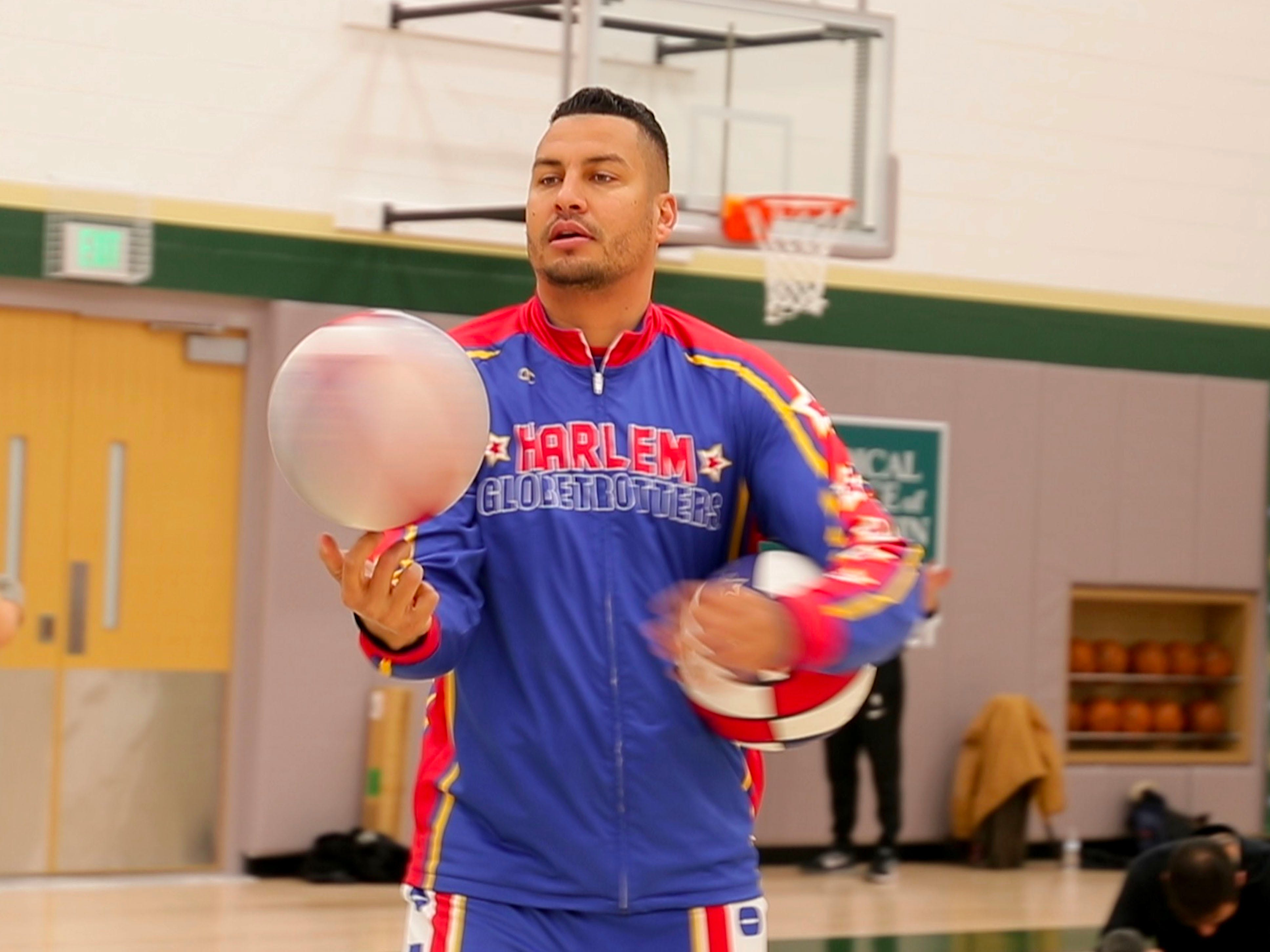 Harlem Globetrotter Orlando El Gato Melendez spins a basketball while doing tricks.