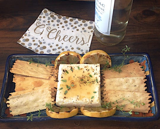 Greek feta cheese is gussied up simply and served with crackers.